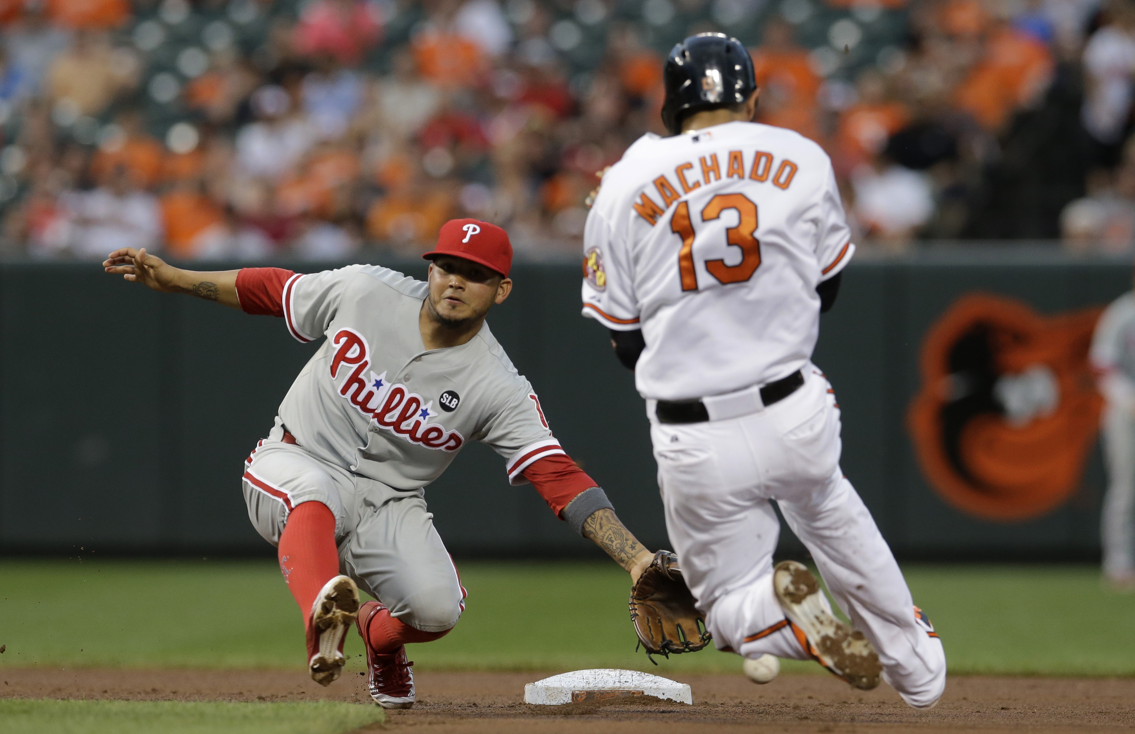 Philadelphia Phillies shortstop Freddy Galvis, left, tries but can't catch a wide throw from catcher Cameron Rupp as Baltimore Orioles' Manny Machado steals second base in the fourth inning of an interleague baseball game, Monday, June 15, 2015, in Baltim