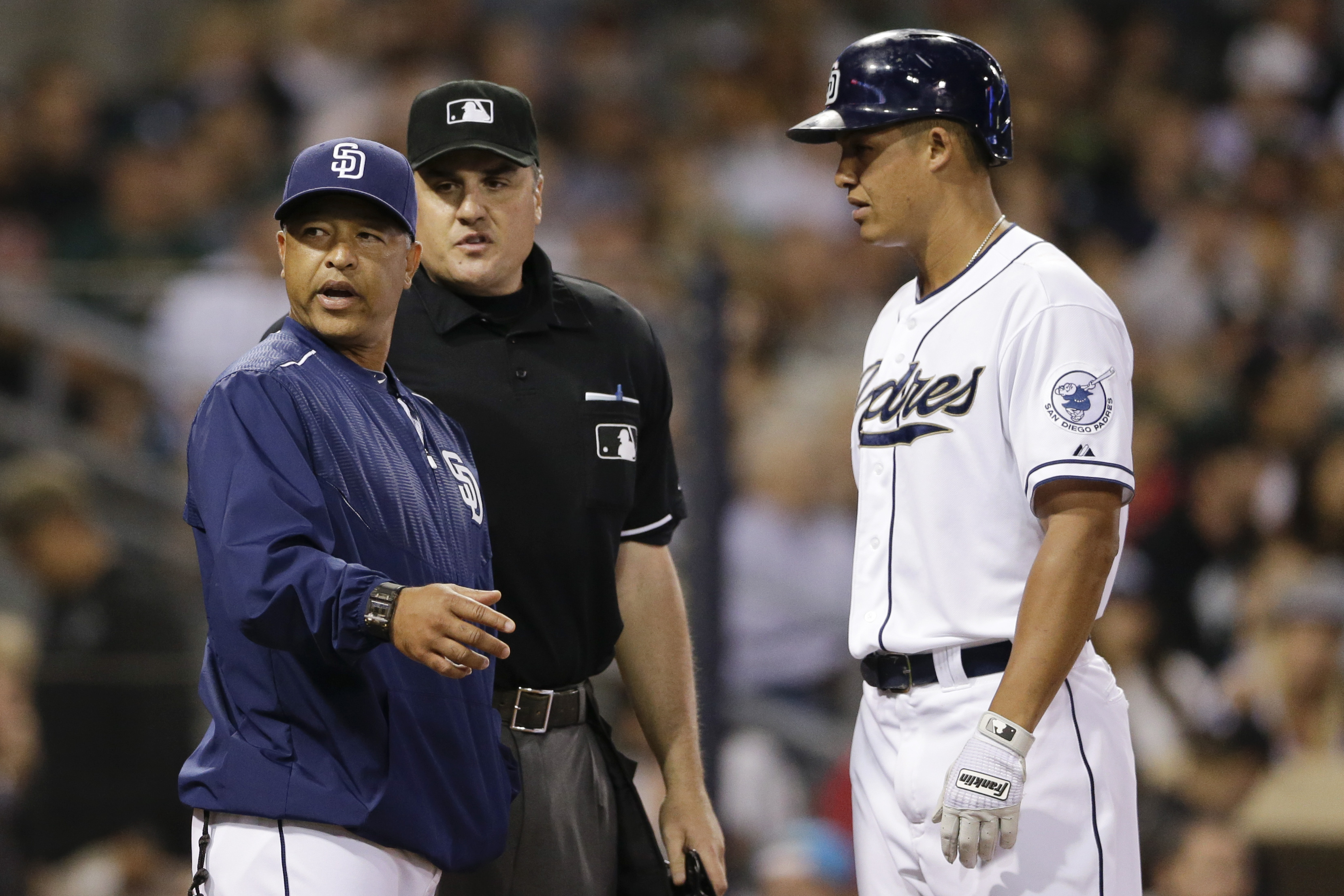 San Diego Padres acting manager Dave Roberts, left, discusses a play with umpire Mike DiMuro, center, as San Diego Padres' Will Venable looks on while playing the Oakland Athletics during the fourth inning of a baseball game Monday, June 15, 2015, in San