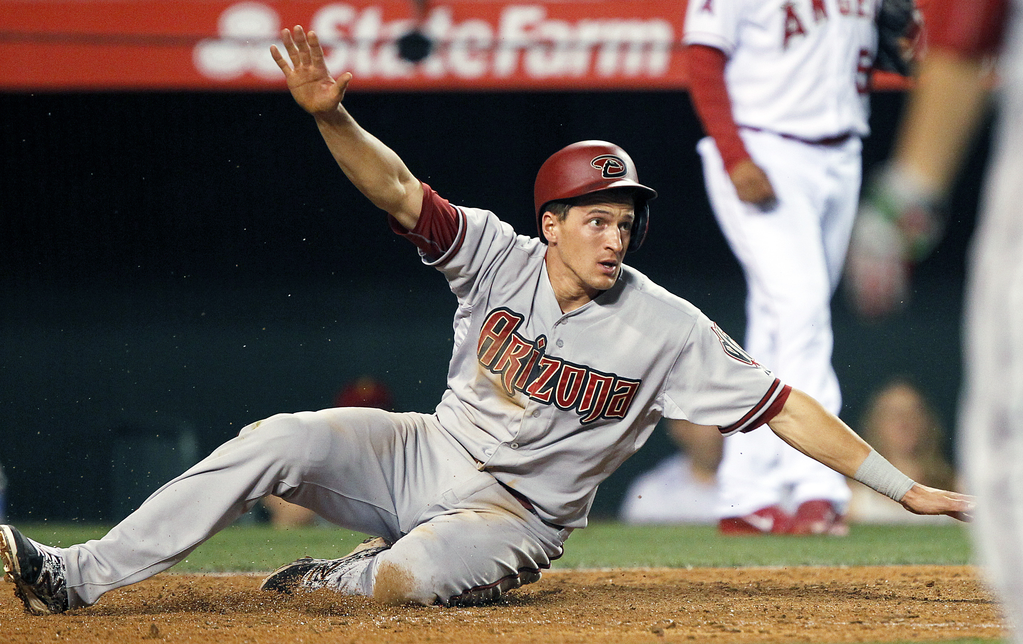 Arizona Diamondbacks' Nick Ahmed signals to the umpire that he is safe, sliding past the tag of Los Angeles Angels catcher Carlos Perez on a sacrifice fly by A.J. Pollock, during the ninth inning of a baseball game in Anaheim, Calif., Monday, June 15, 201