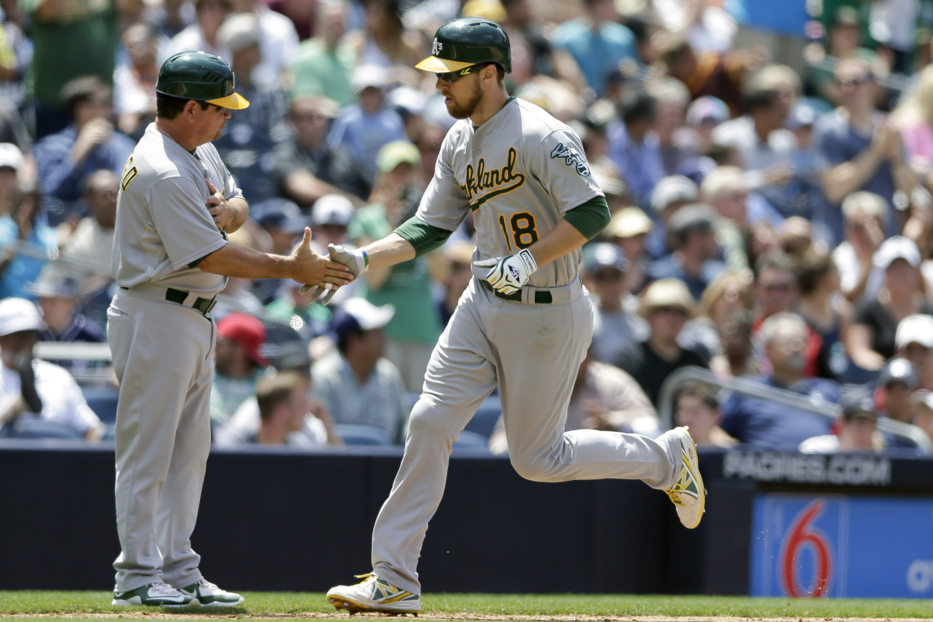 Oakland Athletics' Ben Zobrist (18) is greeted by third base coach Mike Gallego after hitting a two-run home run against the San Diego Padres during the sixth inning of a baseball game Tuesday, June 16, 2015, in San Diego. (AP Photo/Gregory Bull)