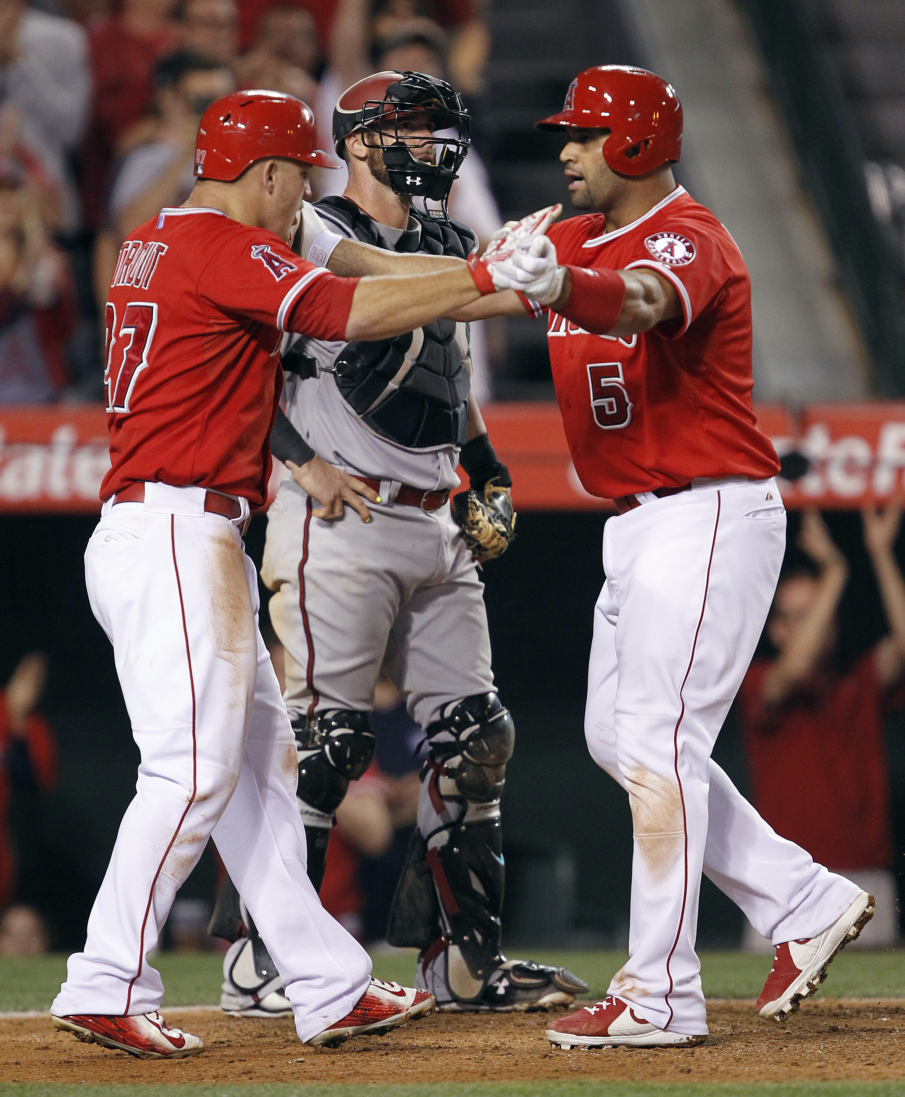 Los Angeles Angels' Mike Trout, left, celebrates with Albert Pujols after a two-run home run by Pujols, next to Arizona Diamondbacks catcher Jarrod Saltalamacchia during the sixth inning of a baseball game in Anaheim, Calif., Tuesday, June 16, 2015. (AP P