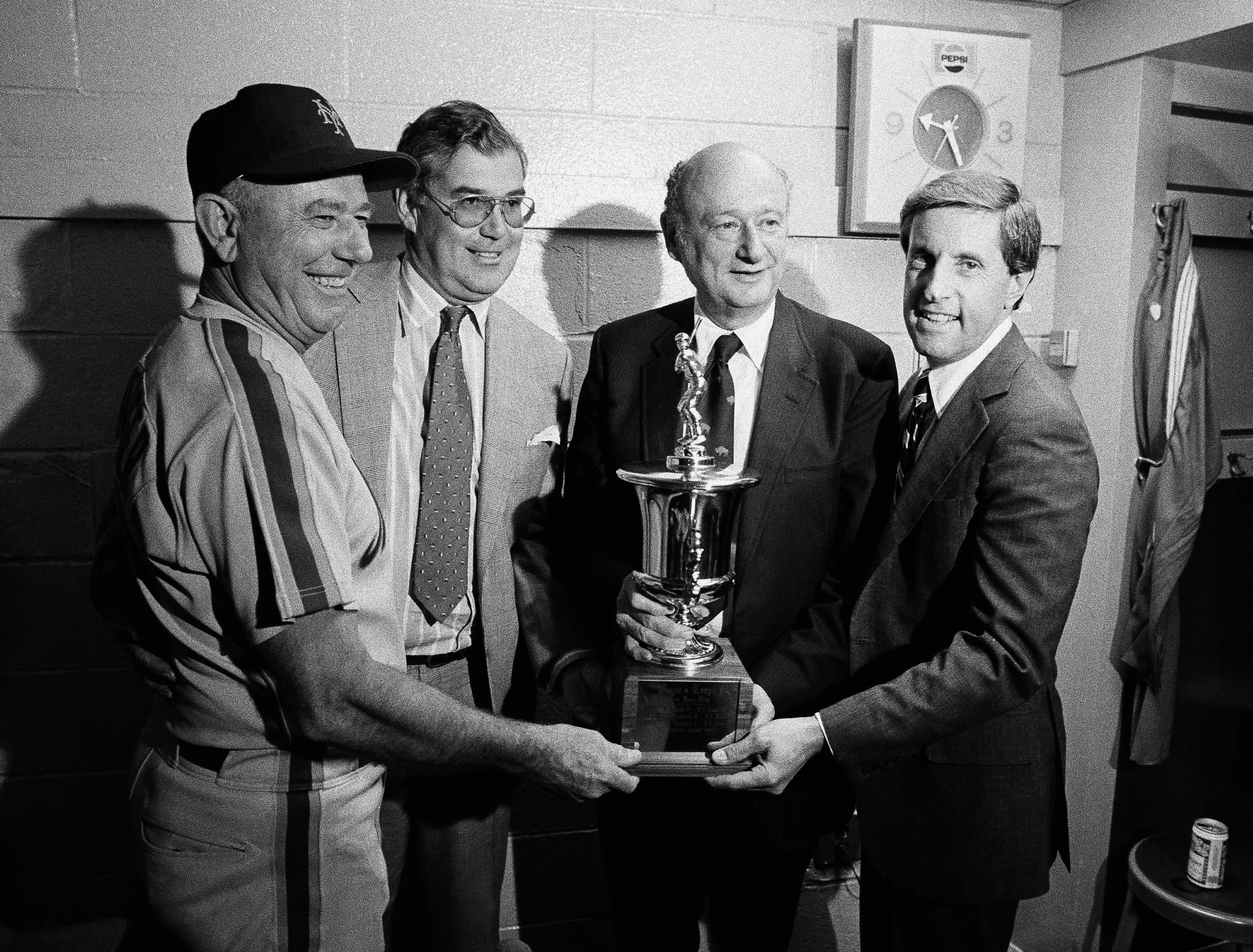 FILE - In this May 27, 1982, file photo, New York Mets management poses with New York City mayor Edward Koch and the Mayor's Trophy in the locker room at Yankee Stadium in New York after the Mets defeated the New York Yankees in an exhibition baseball gam