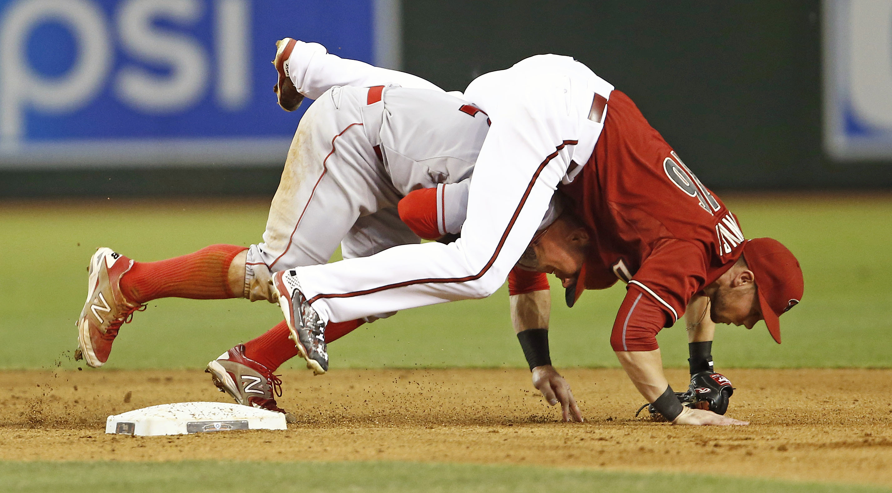 Arizona Diamondbacks' Chris Owings lands on top of Los Angeles Angels' Johnny Giavotella during a double play in the fifth inning of a baseball game in Phoenix,  Wednesday, June 17, 2015. (Rob Schumacher/The Arizona Republic via AP)  MARICOPA COUNTY OUT;