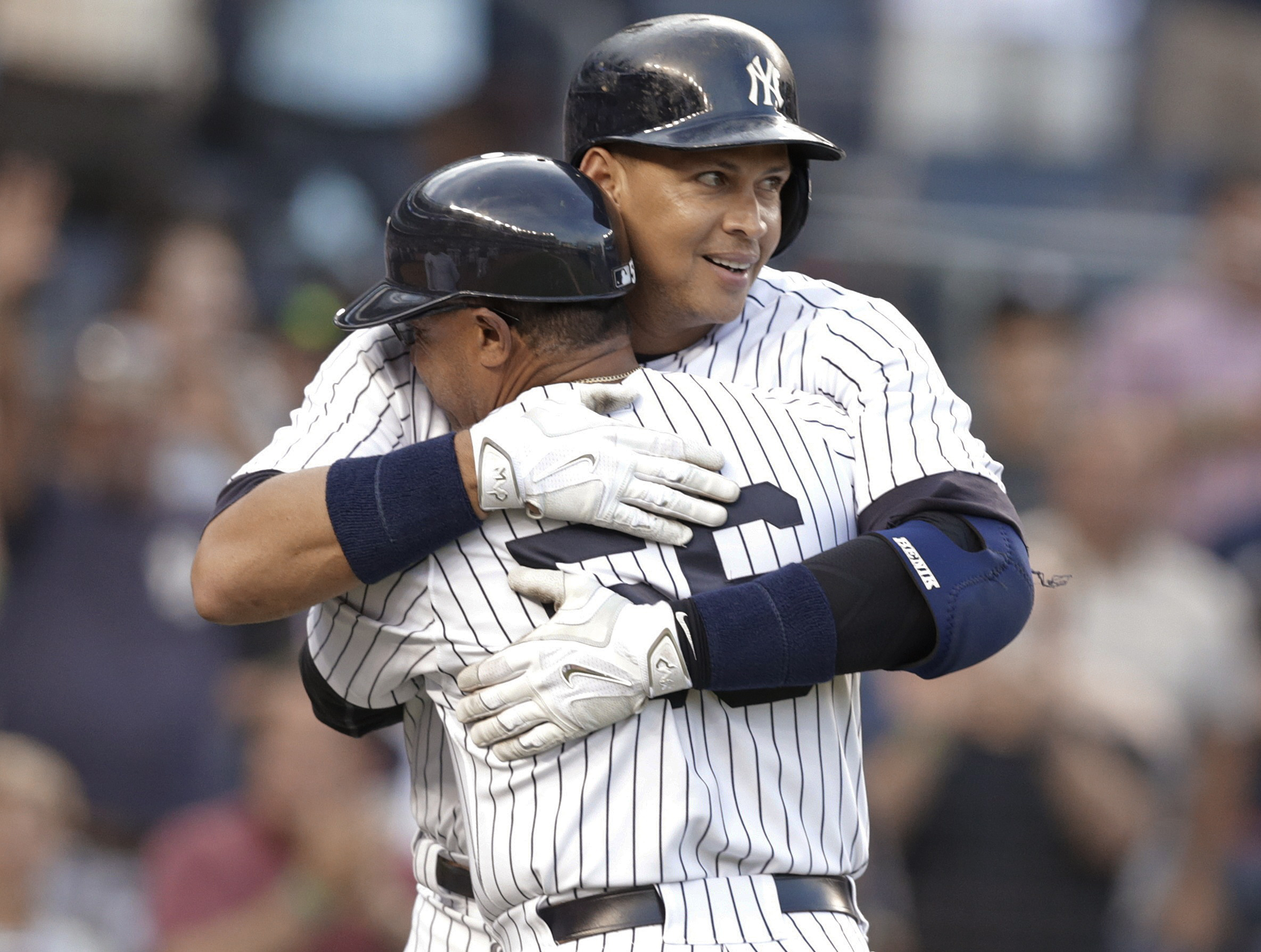 New York Yankees' Alex Rodriguez hugs first base coach Tony Pena after hitting a home run for his 3,000th career hit, during the first inning of a baseball game against the Detroit Tigers on Friday, June 19, 2015, in New York. (AP Photo/Frank Franklin II)