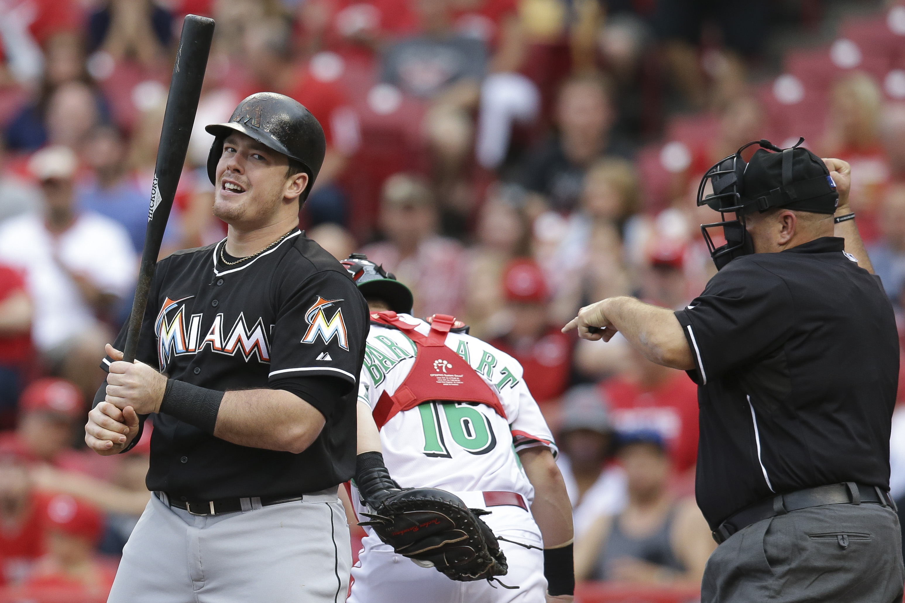 Miami Marlins first baseman Justin Bour reacts after striking out during the second inning of a baseball game against the Cincinnati Reds, Friday, June 19, 2015, in Cincinnati. (AP Photo/John Minchillo)