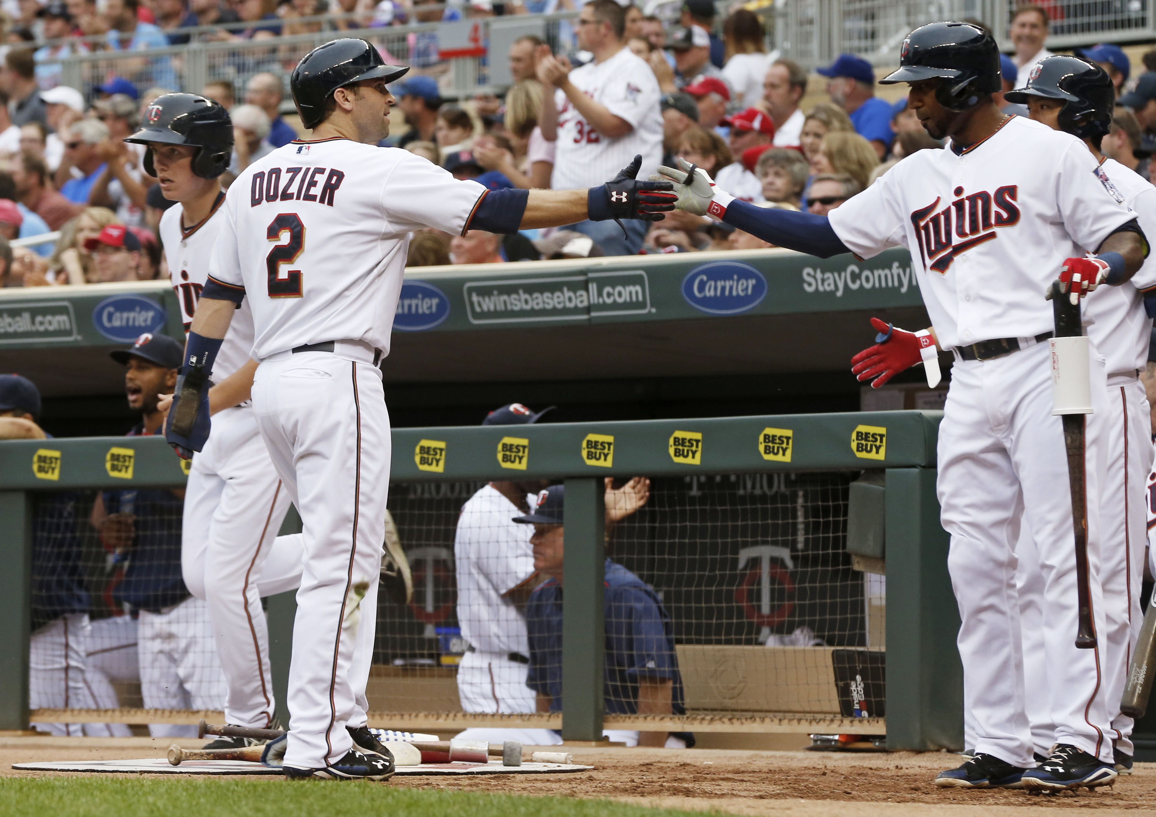 Minnesota Twins' Brian Dozier, left, is congratulated by Eduardo Nunez after he and Eddie Rosario scored on an error by Chicago Cubs' Starlin Castro during the first inning of a baseball game, Friday, June 19, 2015, in Minneapolis.  (AP Photo/Jim Mone)