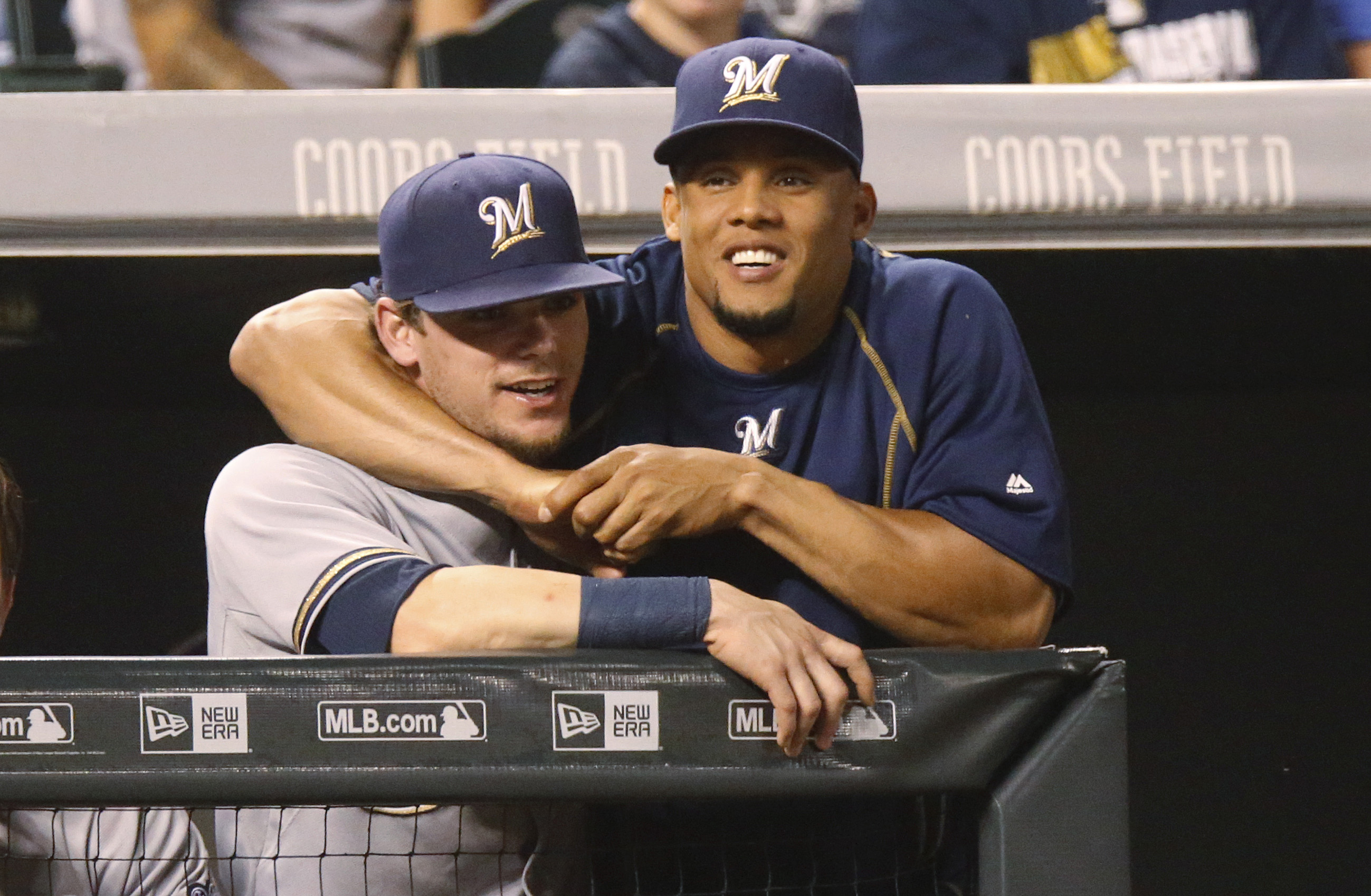 Milwaukee Brewers' Carlos Gomez, right, jokes with second baseman Scooter Gennett as they lean over the dugout rail to watch the Colorado Rockies in the seventh inning of a baseball game Friday, June 19, 2015, in Denver. Milwaukee won 9-5. (AP Photo/David