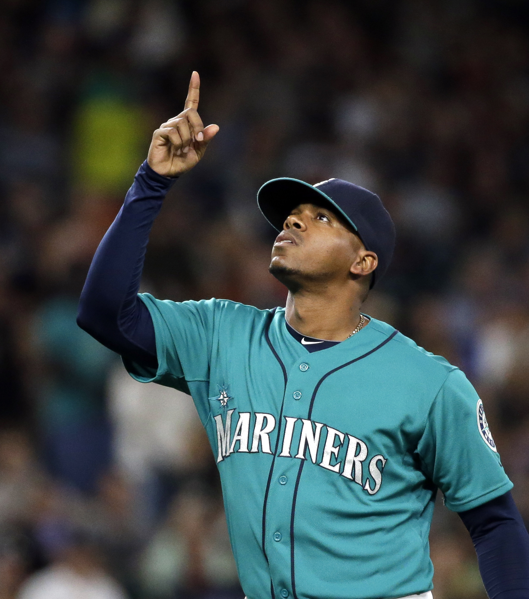 Seattle Mariners starting pitcher Roenis Elias points skyward as he walks off the field after being relieved against the Houston Astros during the eighth inning of a baseball game Friday, June 19, 2015, in Seattle. (AP Photo/Elaine Thompson)