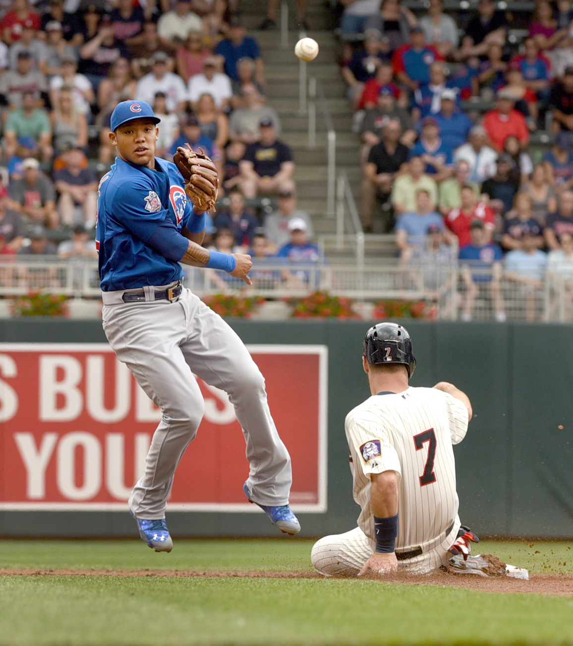 Cubs second baseman Addison Russell doubles off Twins base runner Joe Mauer in the first inning of a baseball game, Saturday, June 20, 2015, in Minneapolis. (AP Photo/Richard Marshall)