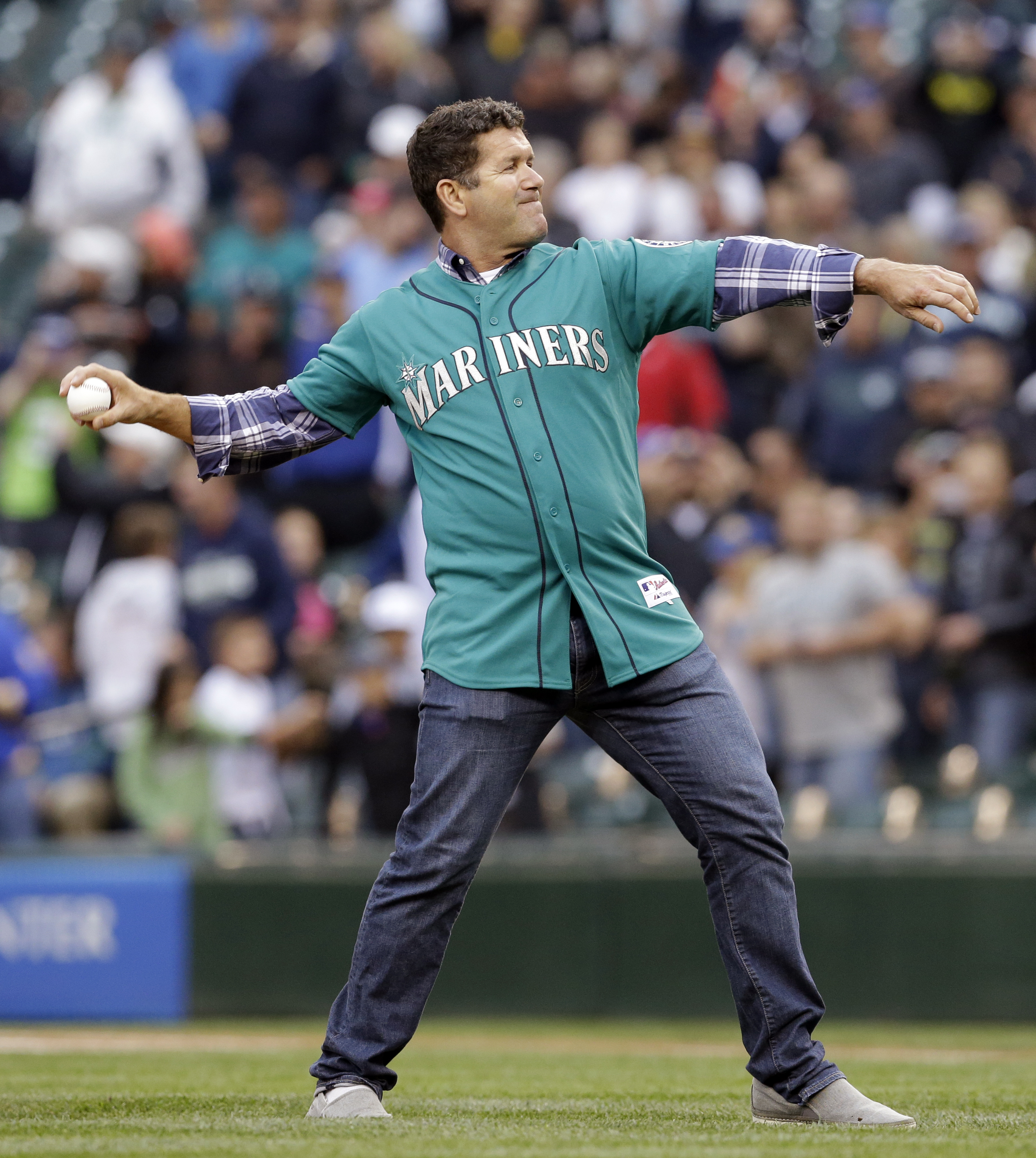 Former Seattle Mariners' Edgar Martinez throws out a ceremonial first pitch before a baseball game against the Texas Rangers Friday, June 13, 2014, in Seattle. (AP Photo/Elaine Thompson)