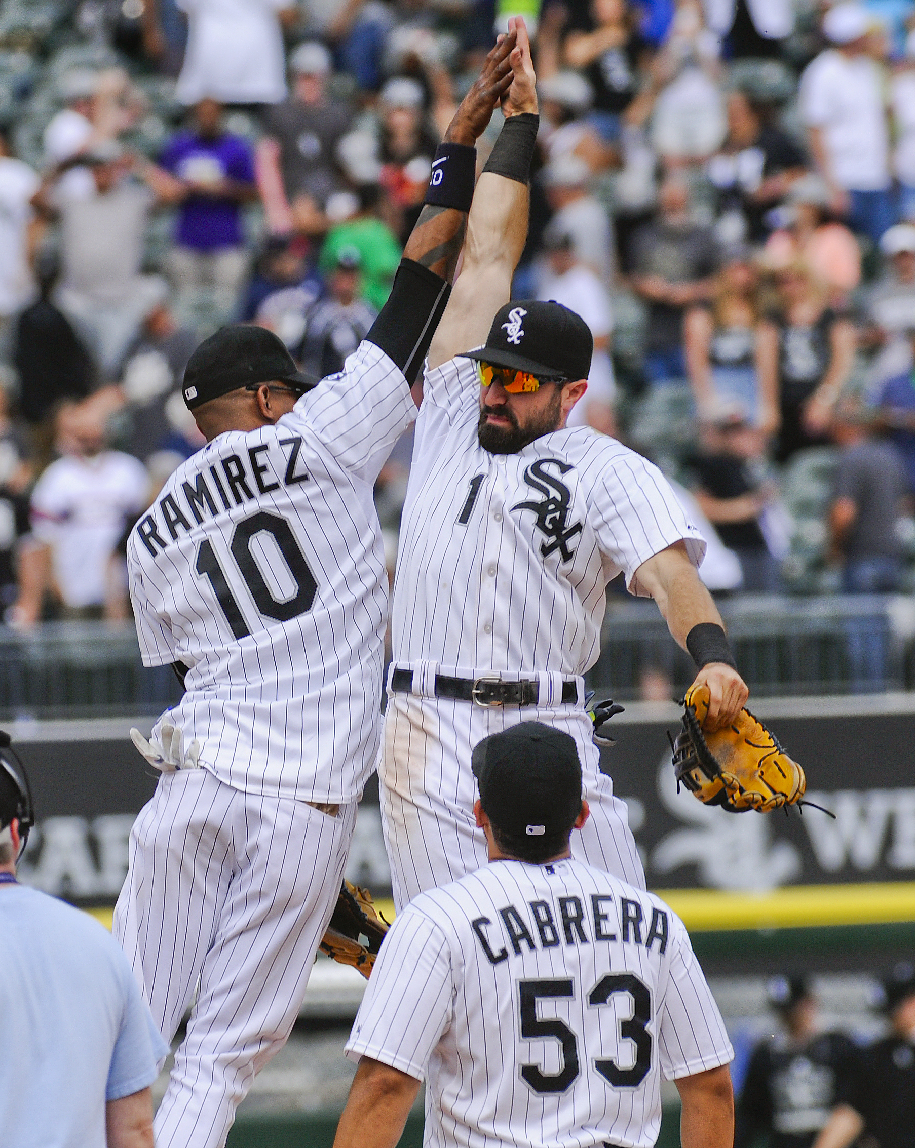 Chicago White Sox's Alexei Ramirez and Chicago White Sox's Adam Eaton (1) high-five as Chicago White Sox's Melky Cabrera (53) watches after they defeated the Texas Rangers 3-2 in a baseball game on Saturday, June 20, 2015, in Chicago. (AP Photo/Matt Marto