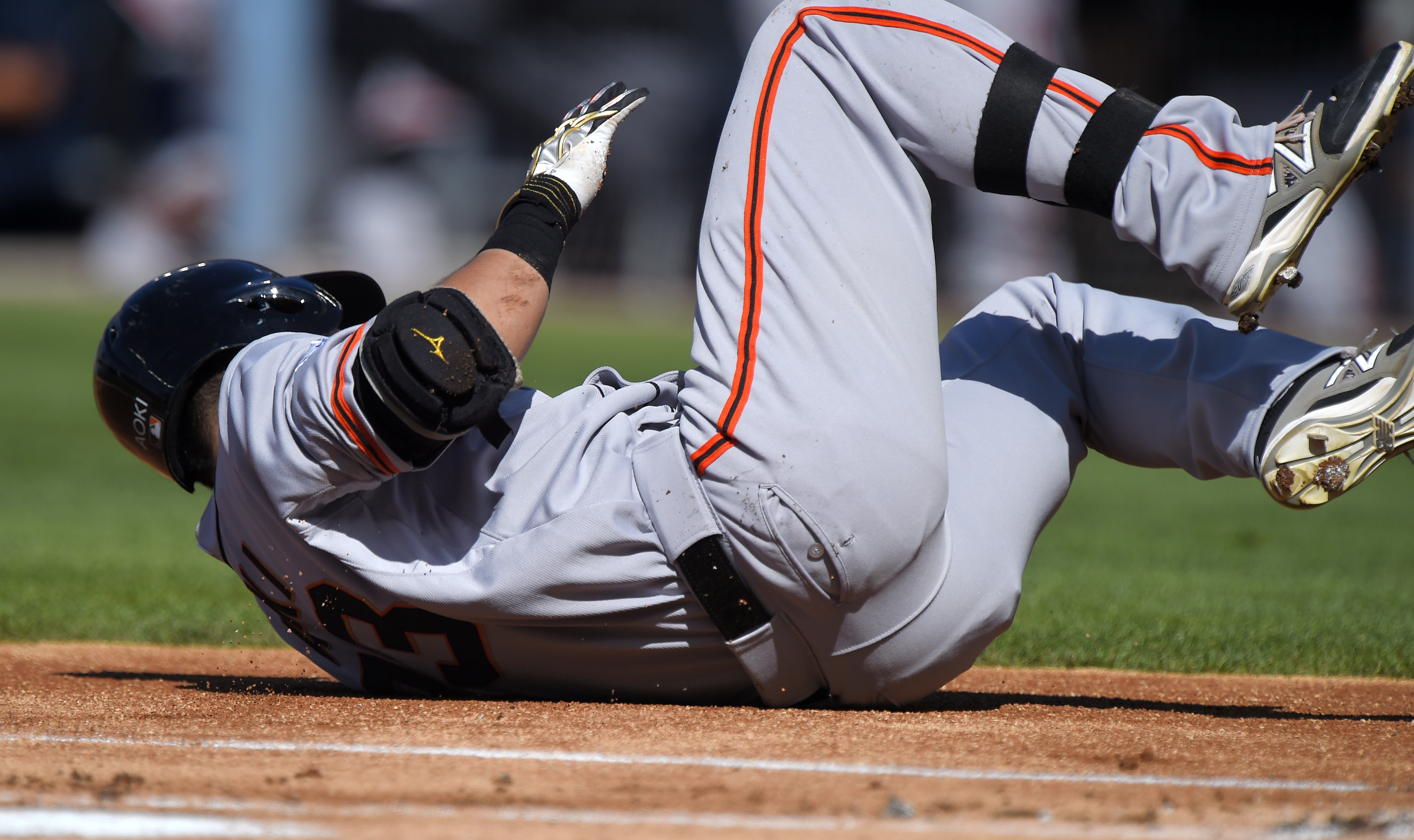 San Francisco Giants' Nori Aoki, of Japan, rolls on the ground after he was hit by a pitch during the first inning of a baseball game against the Los Angeles Dodgers, Saturday, June 20, 2015, in Los Angeles. (AP Photo/Mark J. Terrill)