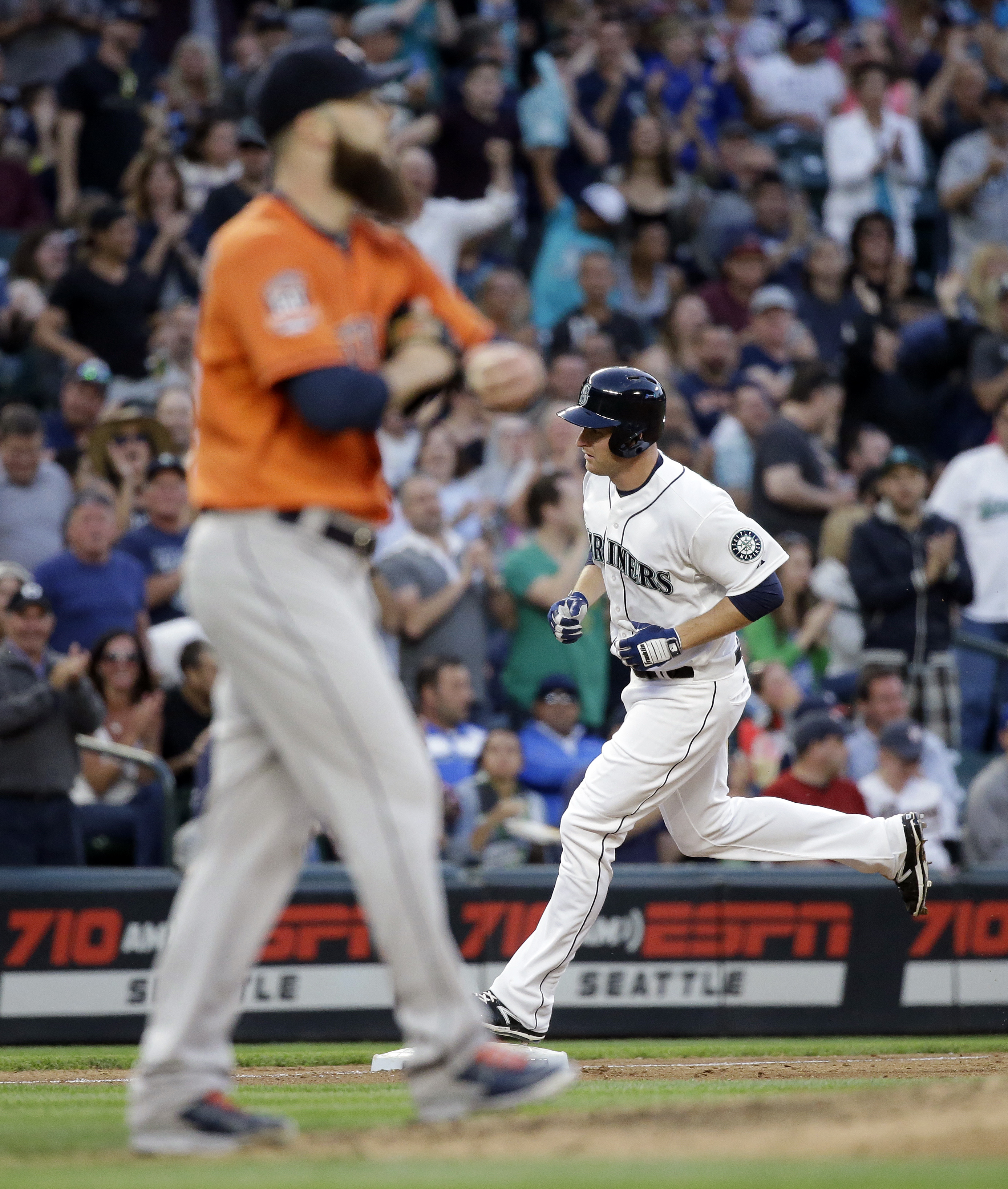 Houston Astros starting pitcher Dallas Keuchel, left, turns away as Seattle Mariners' Mark Trumbo rounds the bases on a home run during the sixth inning of a baseball game Saturday, June 20, 2015, in Seattle. (AP Photo/Elaine Thompson)