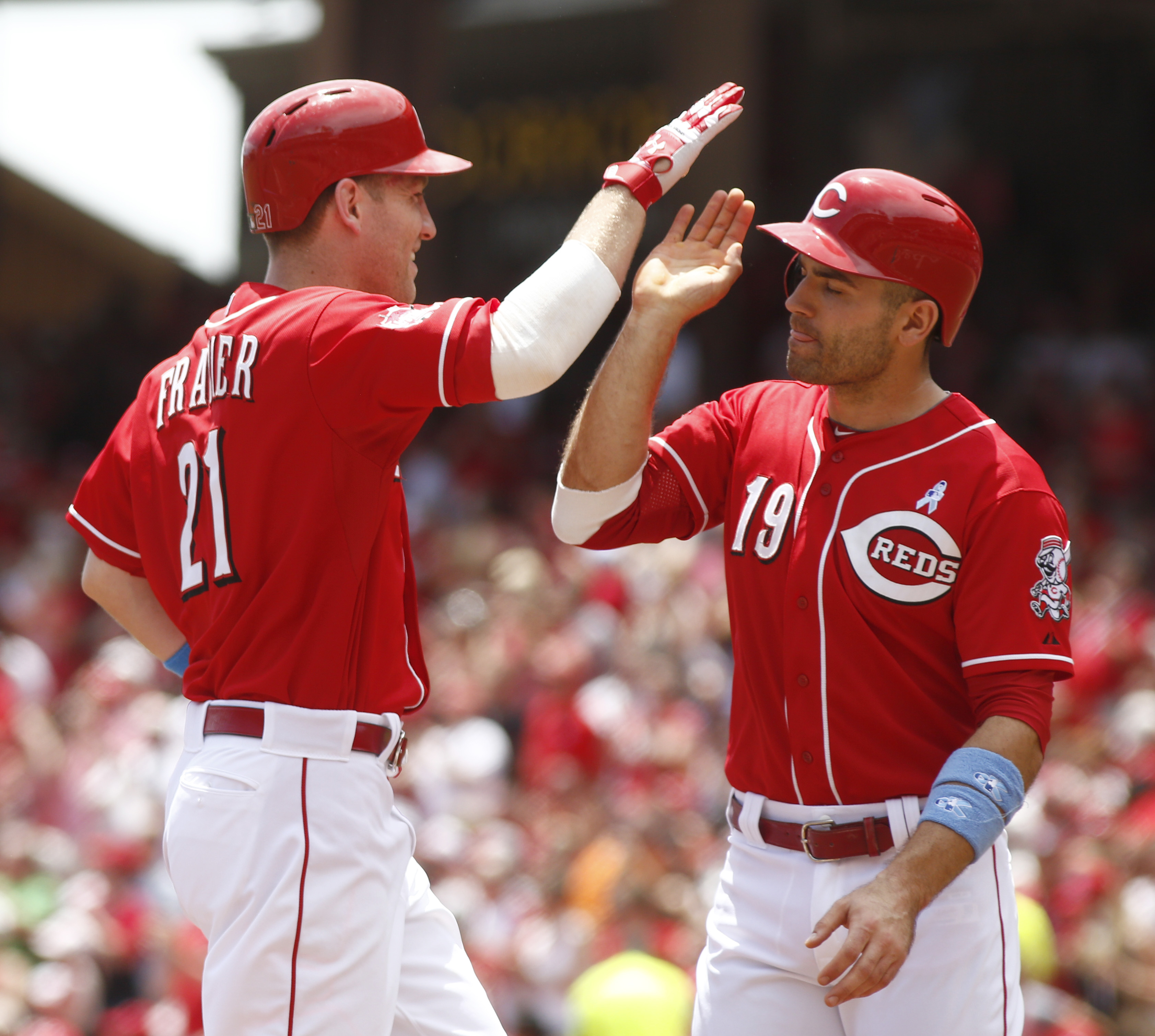 Cincinnati Reds' Todd Frazier (21) is congratulated by Joey Votto (19) after Frazier hit a two-run home run off Miami Marlins starting pitcher David Phelps in the first inning of a baseball game, Sunday, June 21, 2015, in Cincinnati. (AP Photo/David Kohl)