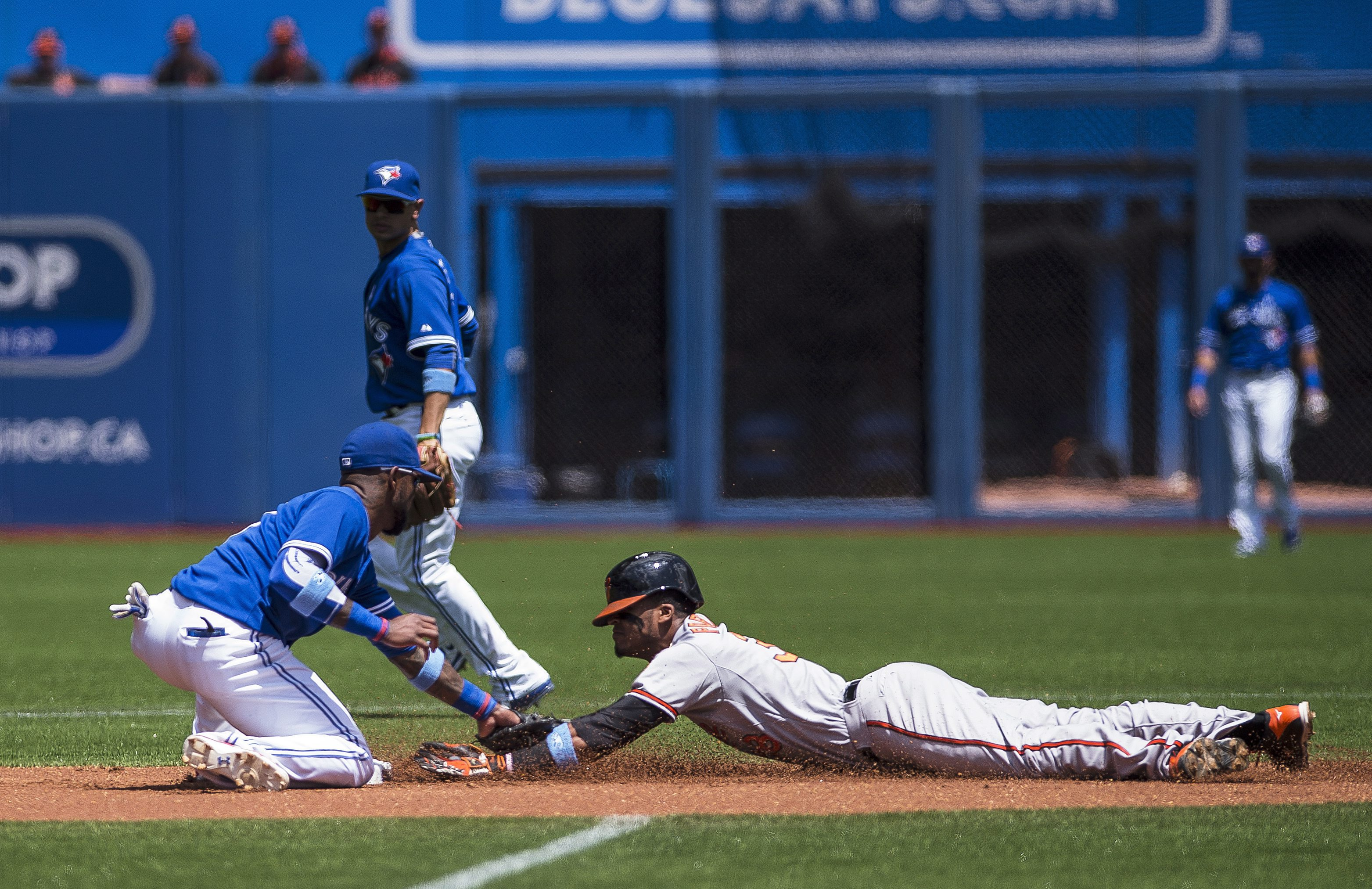 Baltimore Orioles Jimmy Paredes is caught stealing second base by Toronto Blue Jays shortstop Jose Reyes as Jays' Ryan Goins looks on during the first inning of a baseball game in Toronto, Sunday, June 21, 2015. (Aaron Vincent Elkaim/The Canadian Press vi
