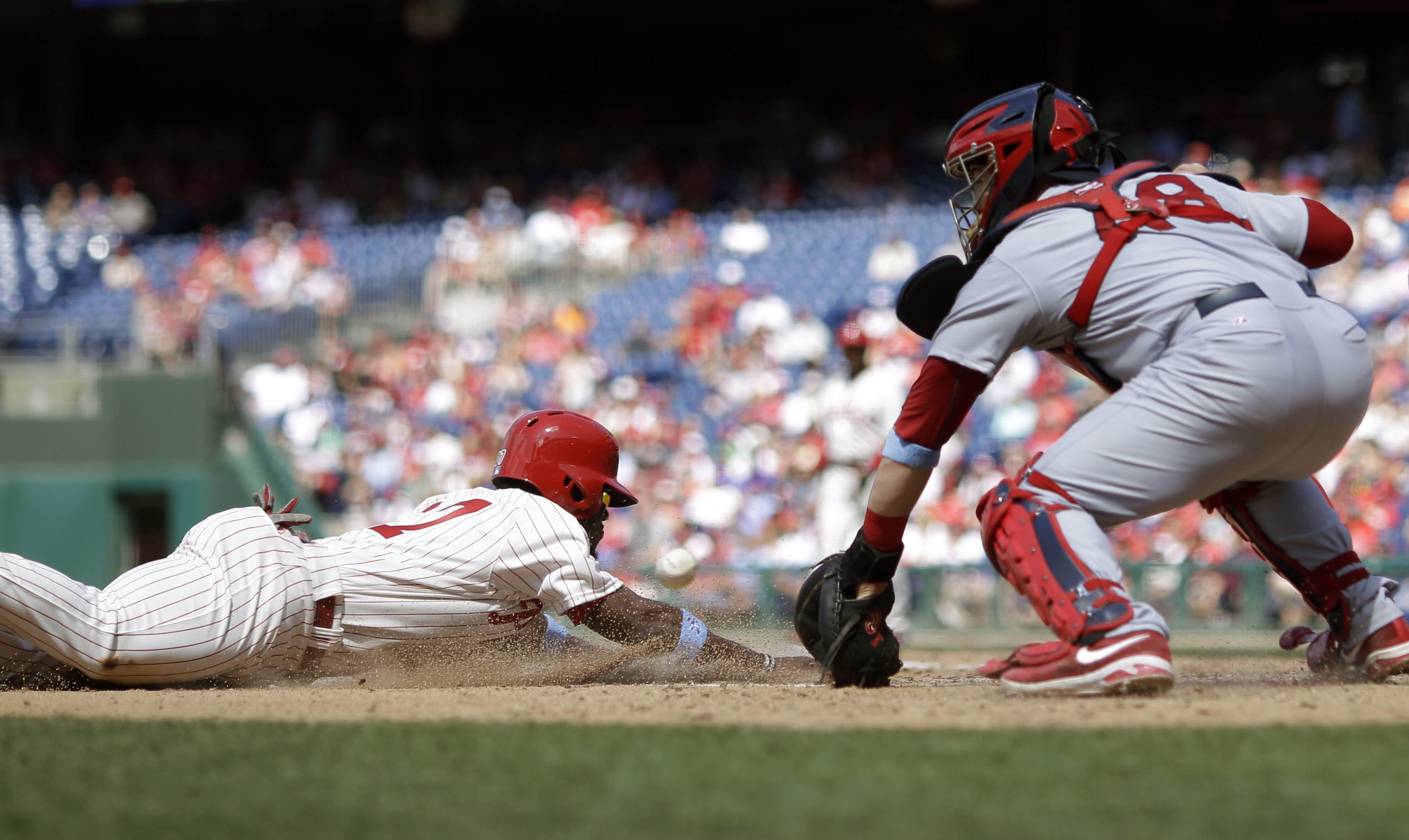 Philadelphia Phillies' Odubel Herrera, left, scores past St. Louis Cardinals catcher Tony Cruz on a single by Ben Revere during the sixth inning of a baseball game, Sunday, June 21, 2015, in Philadelphia. (AP Photo/Matt Slocum)