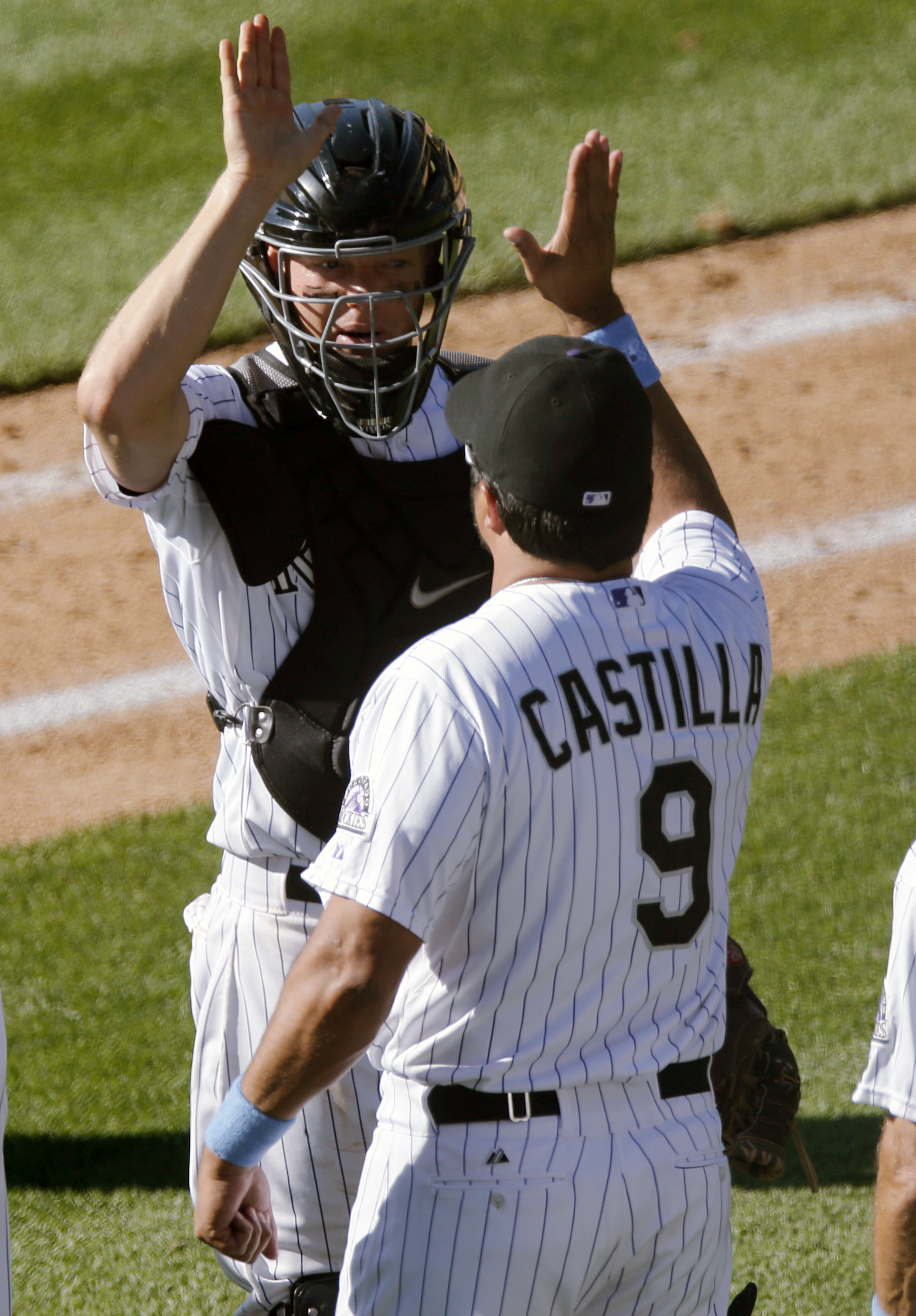 Colorado Rockies catcher Nick Hundley, back, is congratulated by team special assistant Vinny Castilla after retiring the Milwaukee Brewers in the ninth inning of a baseball game Sunday, June 21, 2015, in Denver. Colorado won 10-4. (AP Photo/David Zalubow