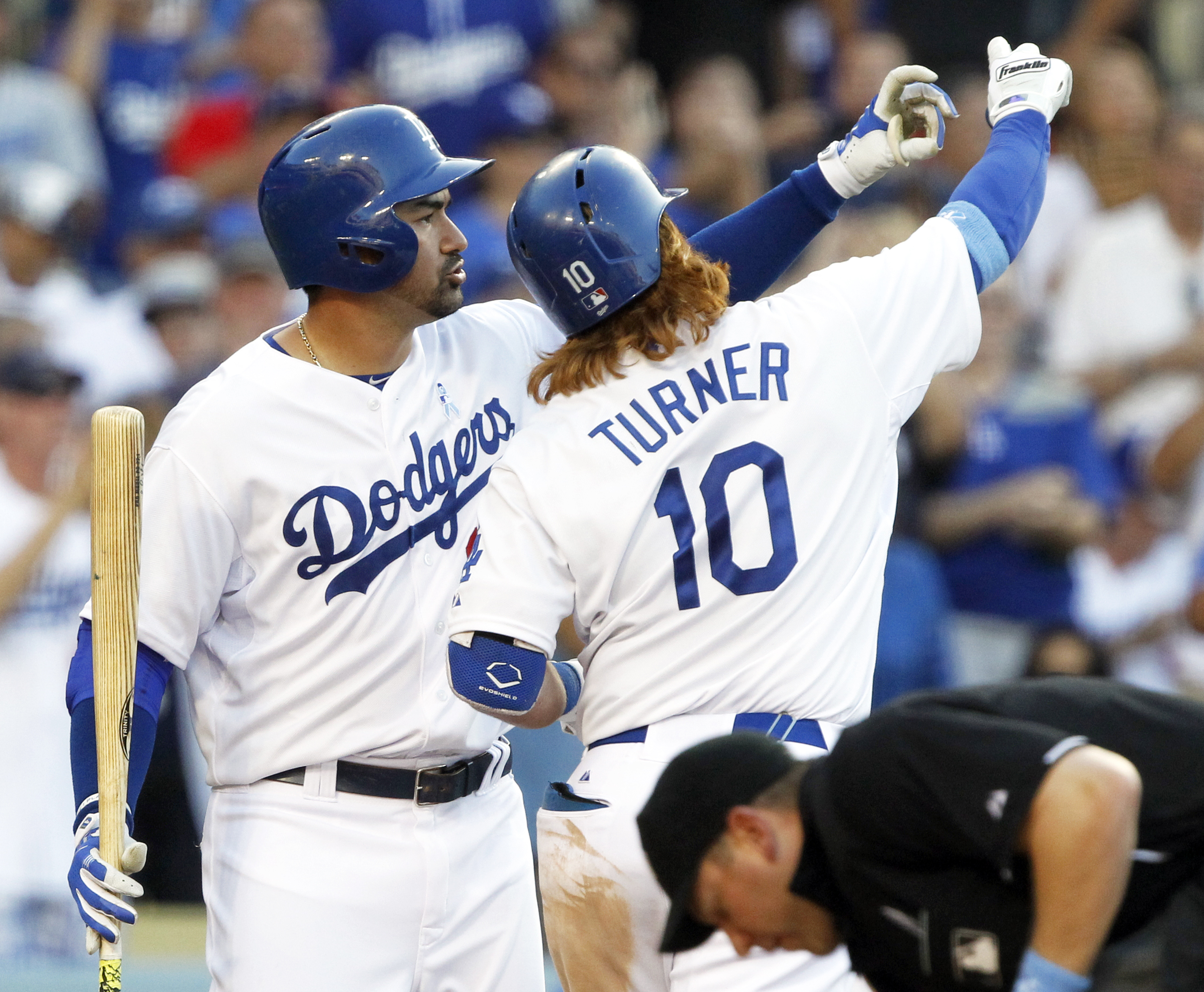 Los Angeles Dodgers' Adrian Gonzalez, left, takes a pretend selfie with Justin Turner after Turner returns after hitting a two-run home run against the San Francisco Giants during the fifth inning of a baseball game in Los Angeles, Sunday, June 21, 2015.