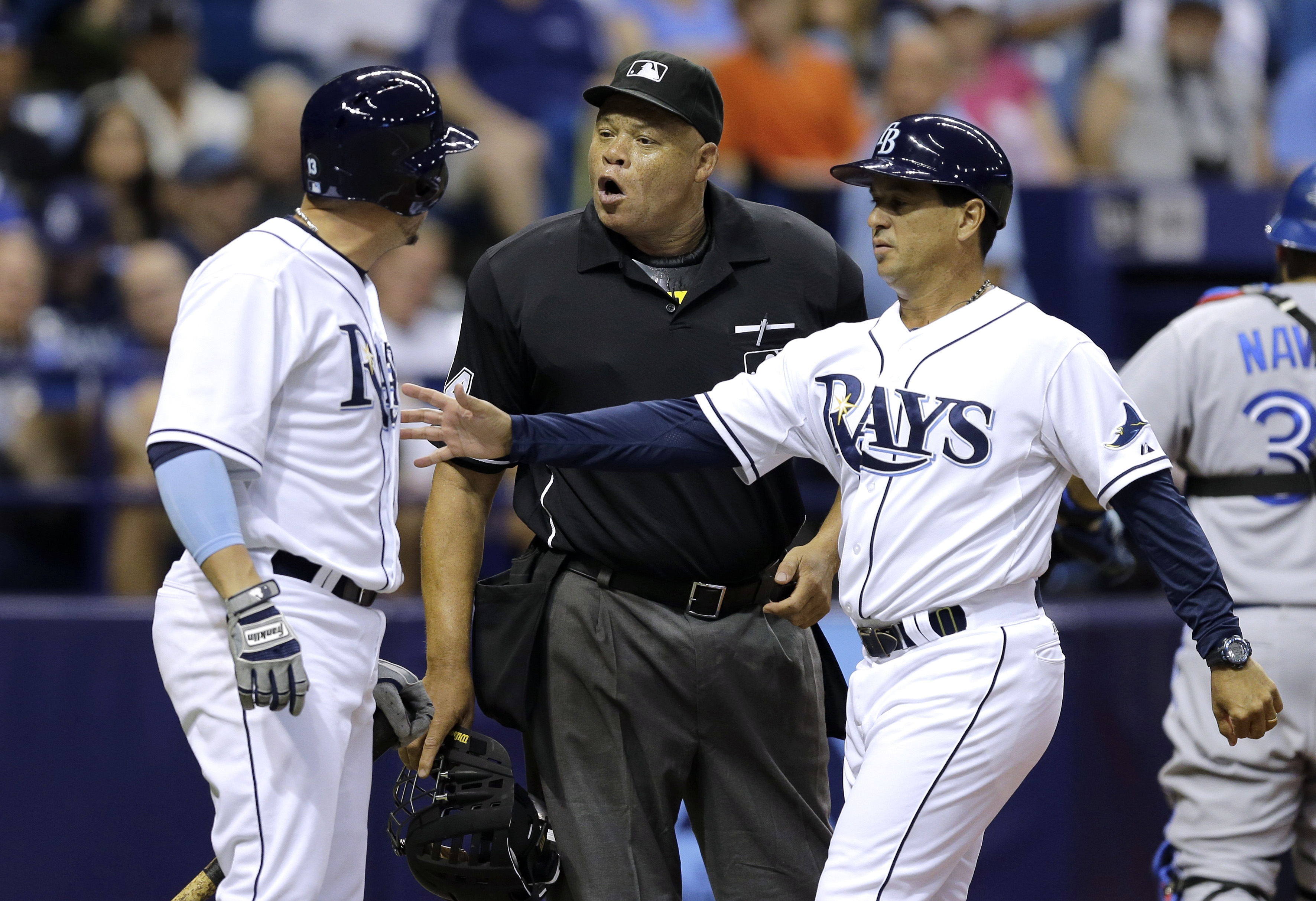 Tampa Bay Rays third base coach Charlie Montoyo, right, restrains Asdrubal Cabrera, left, as he argues a called strike with home plate umpire Kerwin Danley during the fifth inning of a baseball game against the Toronto Blue Jays Monday, June 22, 2015, in