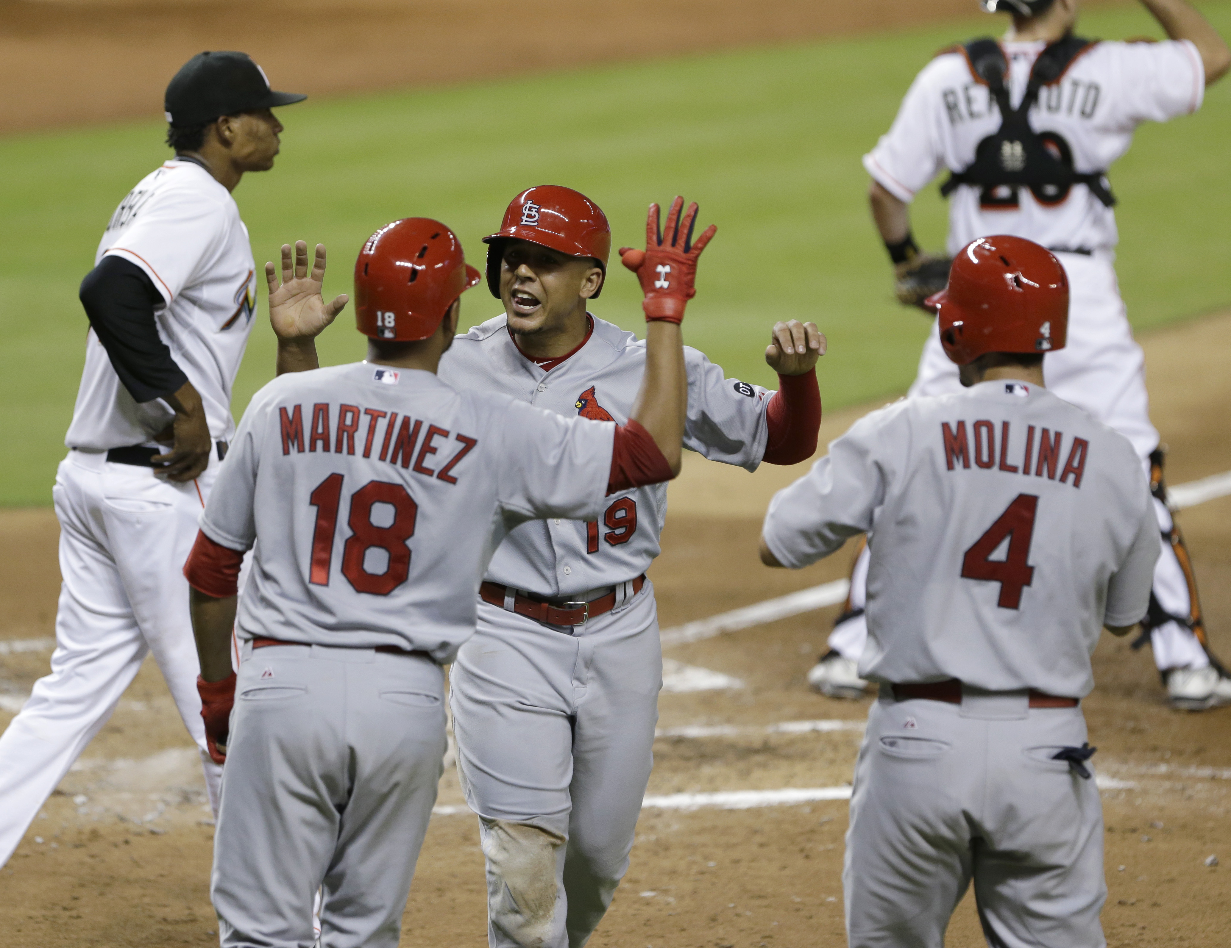 St. Louis Cardinals' Jon Jay (19) celebrates with Carlos Martinez (18) and Yadier Molina (4) after Martinez and Molina scored on a double by Xavier Scruggs during the fourth inning of a baseball game against the Miami Marlins, Tuesday, June 23, 2015, in M