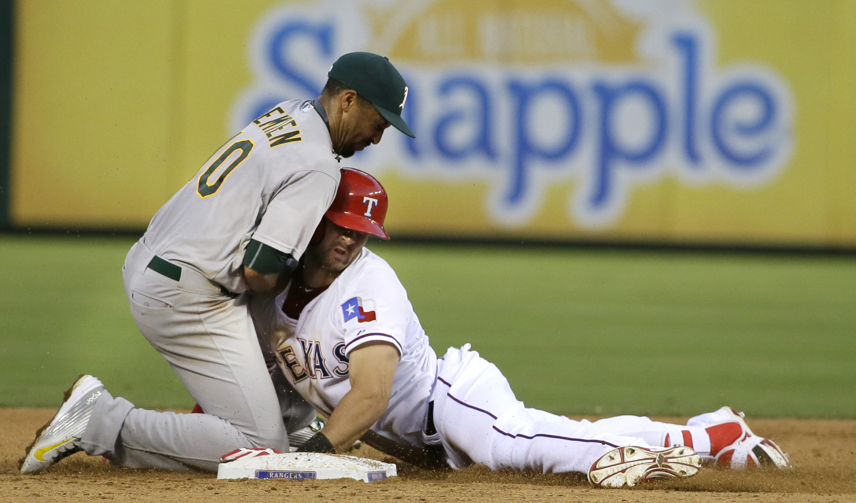 Texas Rangers Joey Gallo, right, slides safely into  Oakland Athletics shortstop Marcus Semien (10) for a double during the fifth inning of a baseball game in Arlington, Texas, Tuesday, June 23, 2015. (AP Photo/LM Otero)