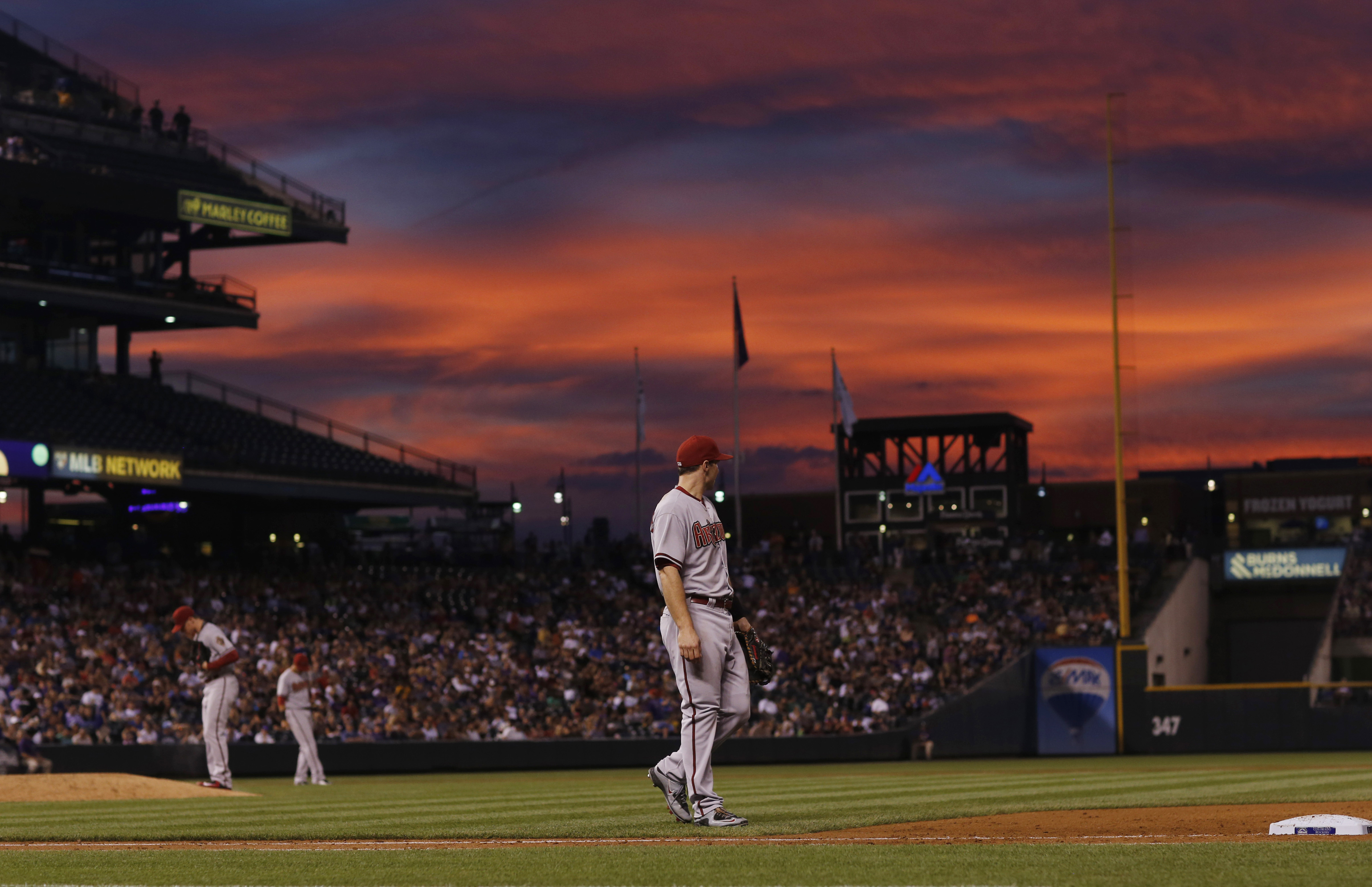 As the setting sun illuminates the sky in the background, Arizona Diamondbacks first baseman Paul Goldschmidt heads back to his position after pursuing a sacrifice bunt put down by Colorado Rockies pitcher Kyle Kendrick during the fifth inning of a baseba
