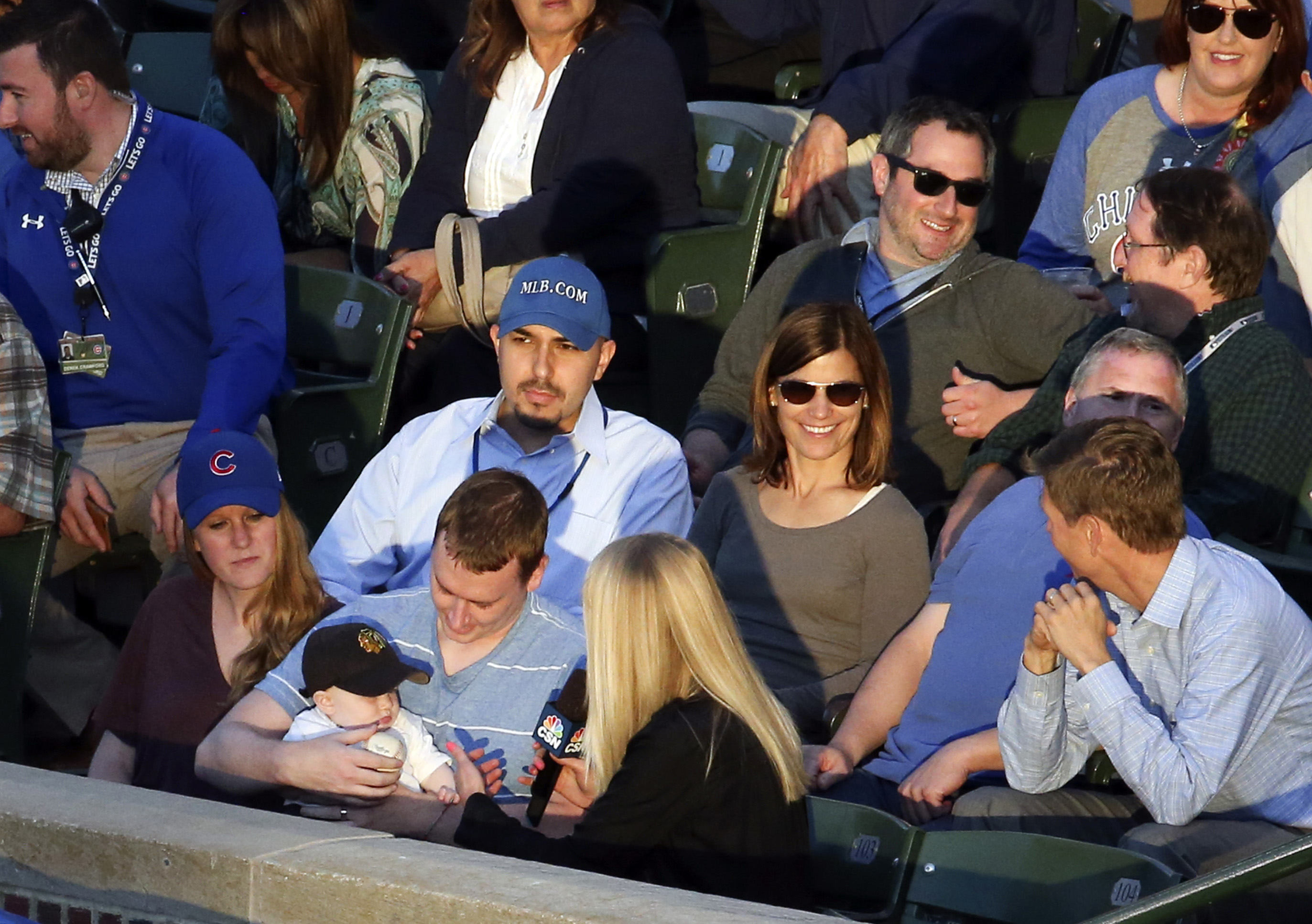 In this photo taken Tuesday, June 23, 2015, Keith Hartley, second left,is interviewed by a television reporter after he caught a foul ball while bottle-feeding his 7-month-old son during a baseball game between the Chicago Cubs and the Los Angeles Dodgers