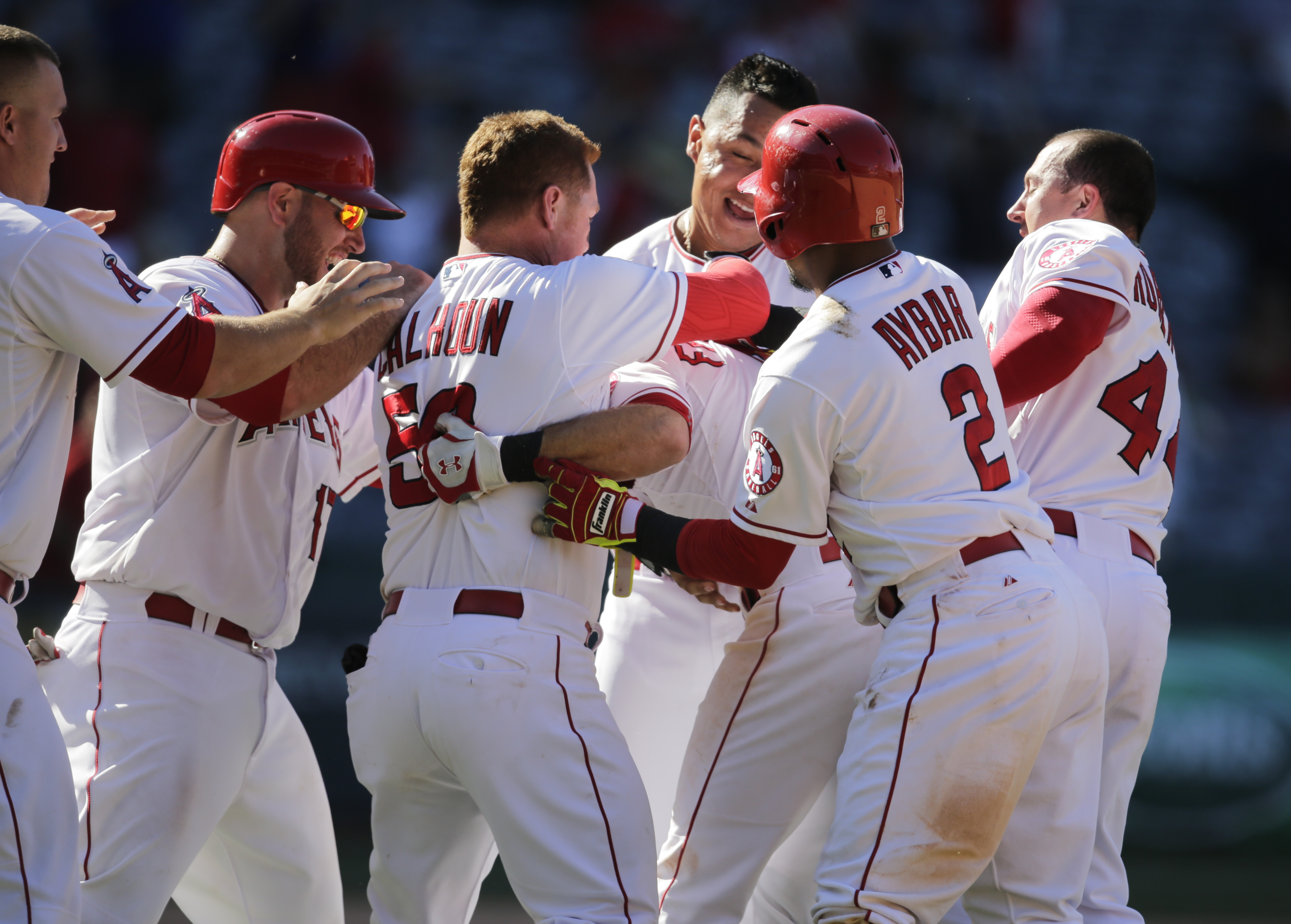Los Angeles Angels players celebrate Taylor Featherston's walk-off single in the 13th inning of a baseball game against the Houston Astros, Wednesday, June 24, 2015, in Anaheim, Calif. The Angels won 2-1. (AP Photo/Jae C. Hong)
