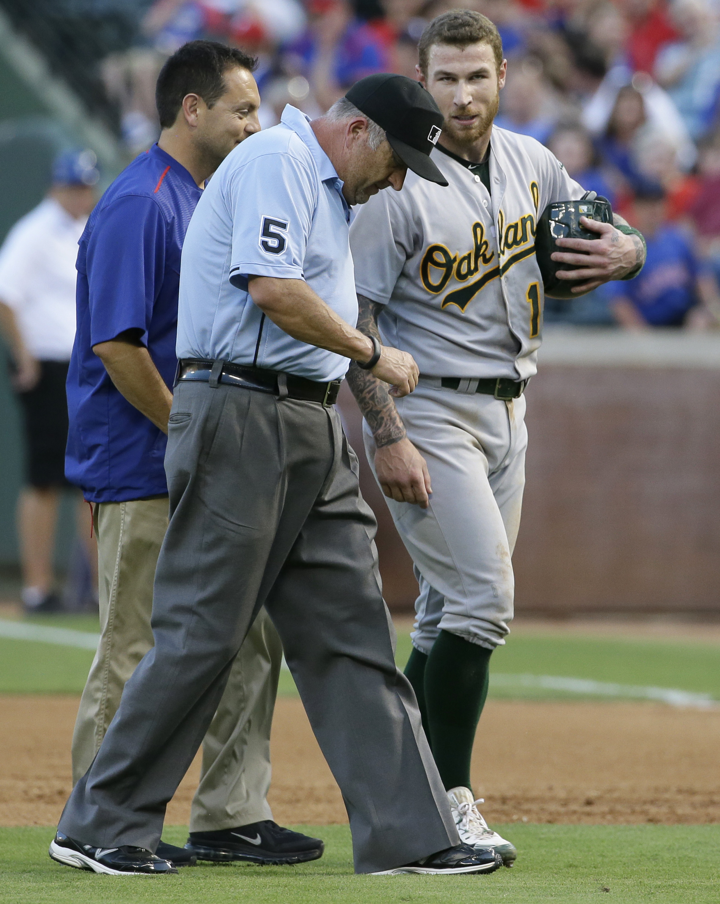Umpire Dale Scott, front, leaves the game as  Oakland Athletics Brett Lawrie (15) checks on him after Scott was struck by a line drive during the fourth inning of a baseball game between the Oakland Athletics and Texas Rangers in Arlington, Texas, Wednesd
