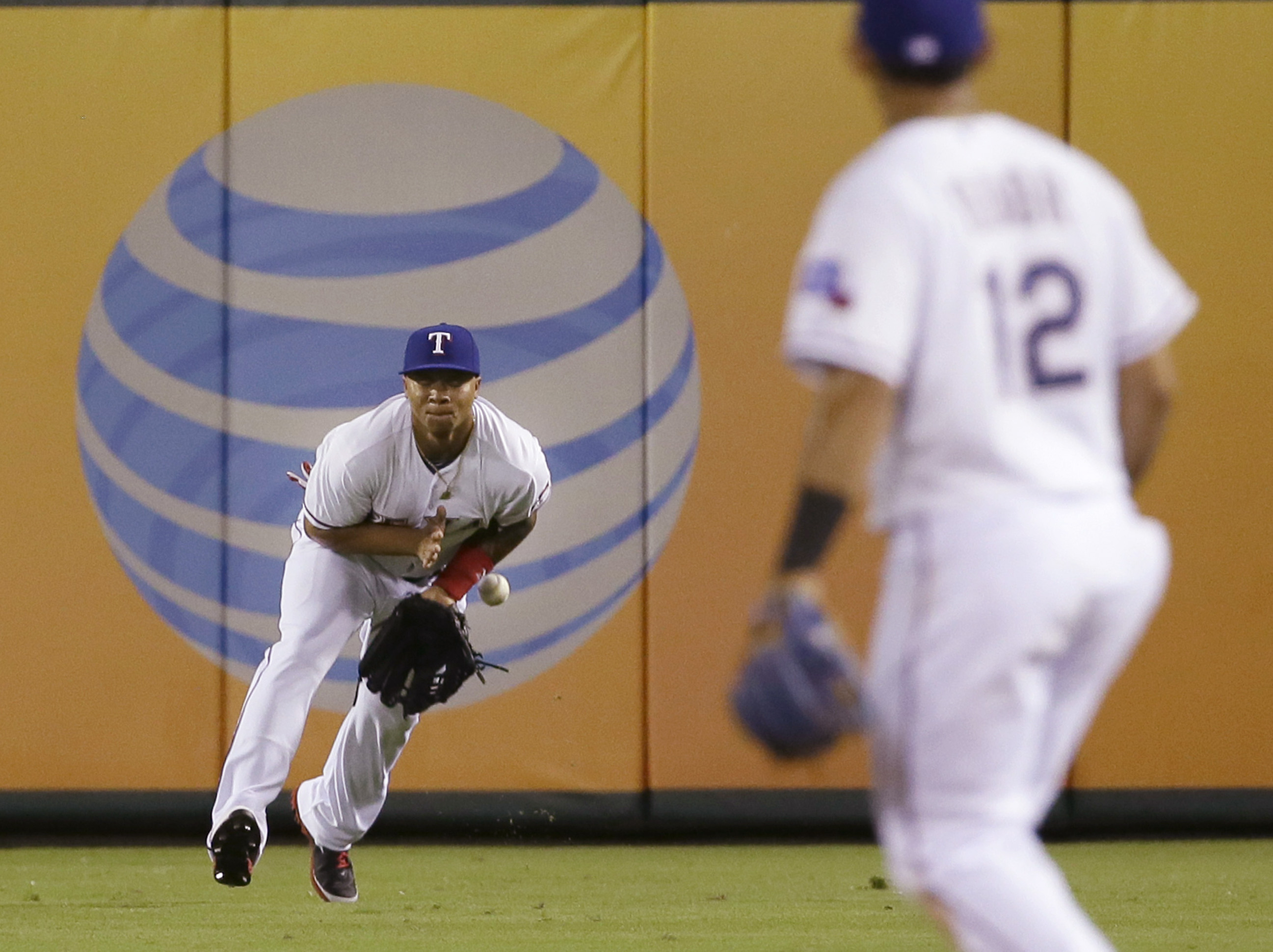 Texas Rangers right fielder Michael Choice, left, commits a fielding error on a single by Oakland Athletics Stephen Vogt during the eighth inning of a baseball game in Arlington, Texas, Wednesday, June 24, 2015. Vogt advanced to third base on the play. Th
