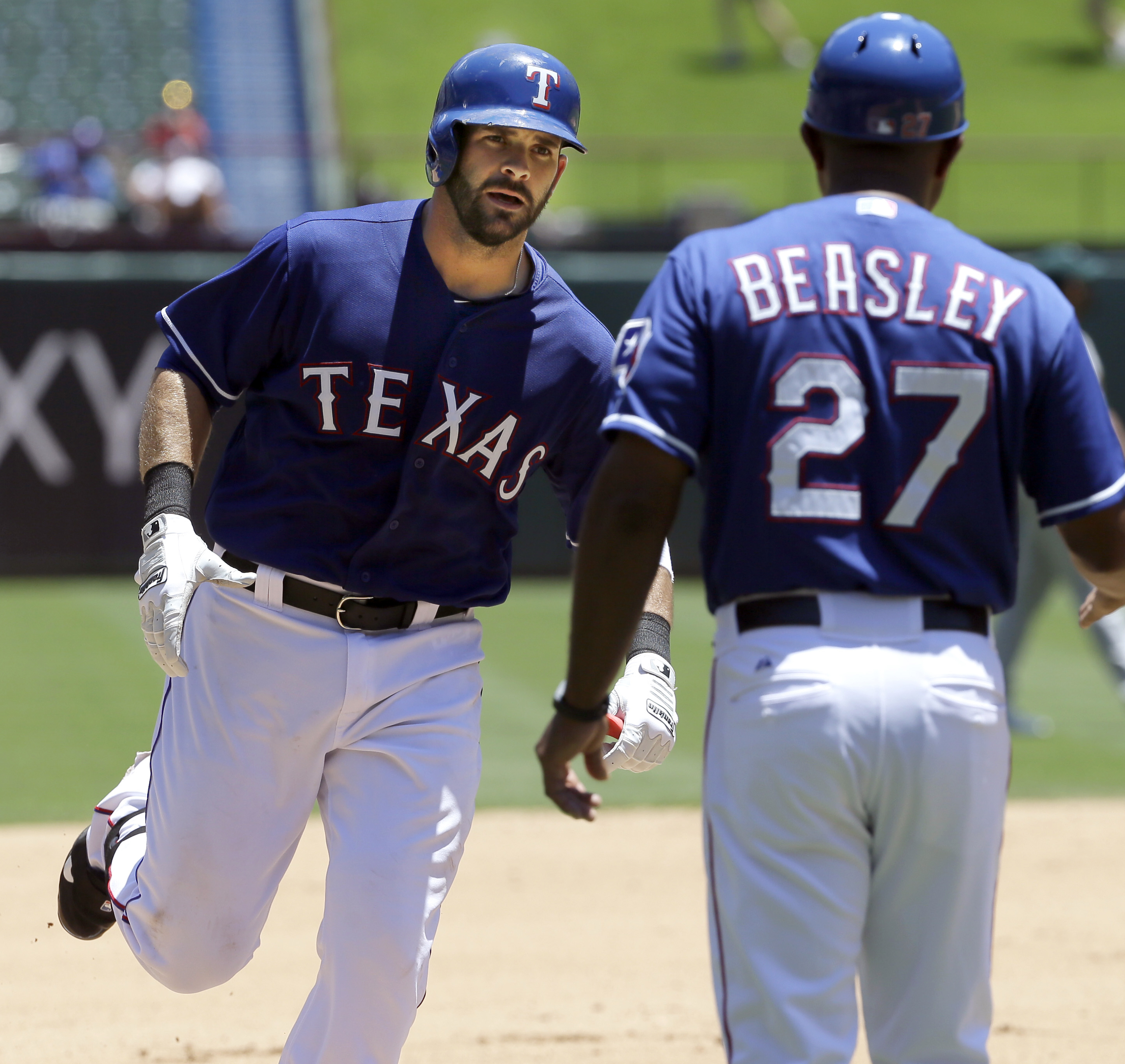 Texas Rangers' Mitch Moreland, left, is greeted by third base coach Tony Beasley as he rounds the bases after hitting a solo home run during the fourth inning of a baseball game against the Oakland Athletics, Thursday, June 25, 2015, in Arlington, Texas.