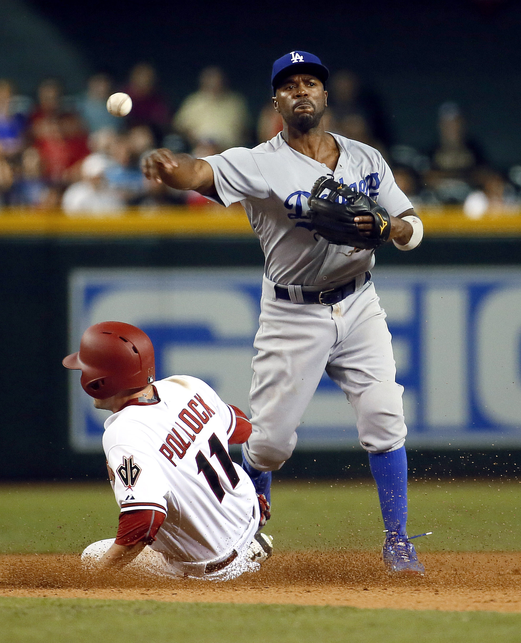 Los Angeles Dodgers shortstop Jimmy Rollins forces out Arizona Diamondbacks' A.J. Pollock while turning a double play on Diamondbacks' David Peralta during the seventh inning of a baseball game, Tuesday, June 30, 2015, in Phoenix. (AP Photo/Matt York)