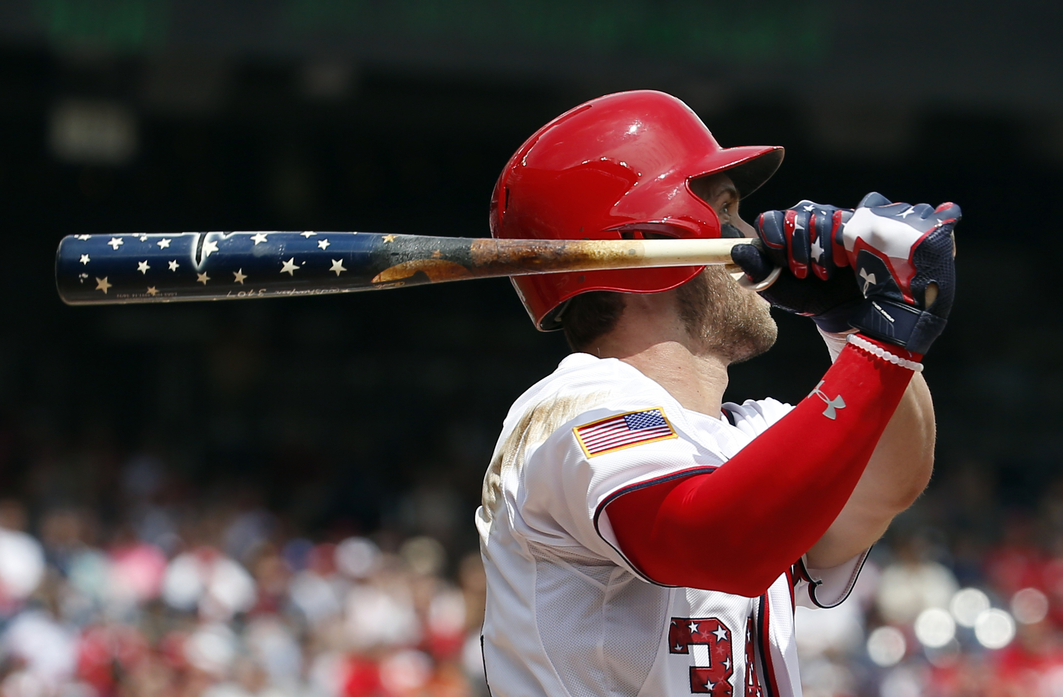 Washington Nationals' Bryce Harper (34) watches his two-run homer as he holds his Independence Day themed bat during the first inning of a baseball game against the San Francisco Giants at Nationals Park, Saturday, July 4, 2015, in Washington. (AP Photo/A