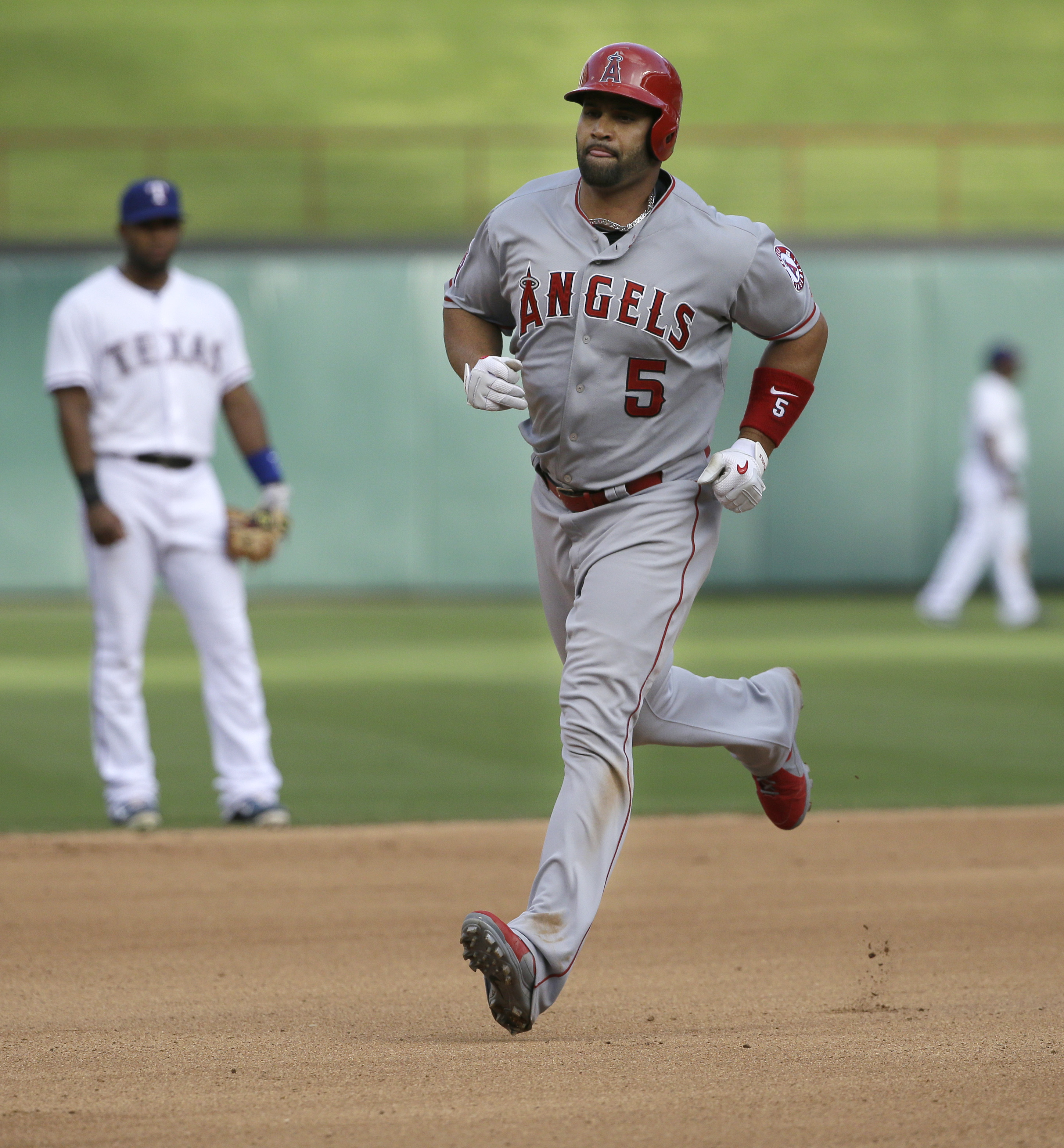 Los Angeles Angels Albert Pujols (5) runs the bases after his solo home run as Texas Rangers shortstop Elvis Andrus, left, looks on in the background during the fourth inning of a baseball game in Arlington, Texas, Sunday, July 5, 2015. (AP Photo/LM Otero
