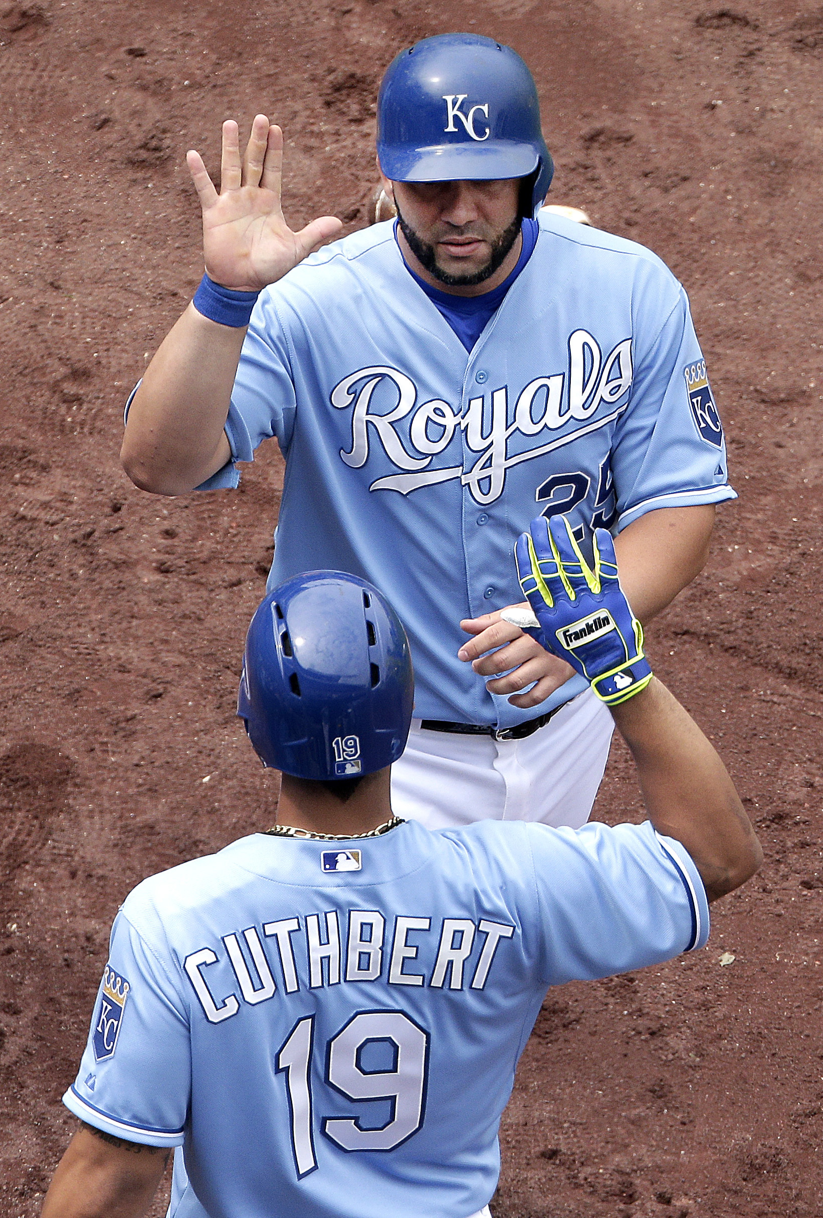 Kansas City Royals' Kendrys Morales (25) and Cheslor Cuthbert (19) celebrate after Morales scored on a single by Omar Infante during the seventh inning of the first game in a baseball doubleheader against the Tampa Bay Rays Tuesday, July 7, 2015, in Kansa
