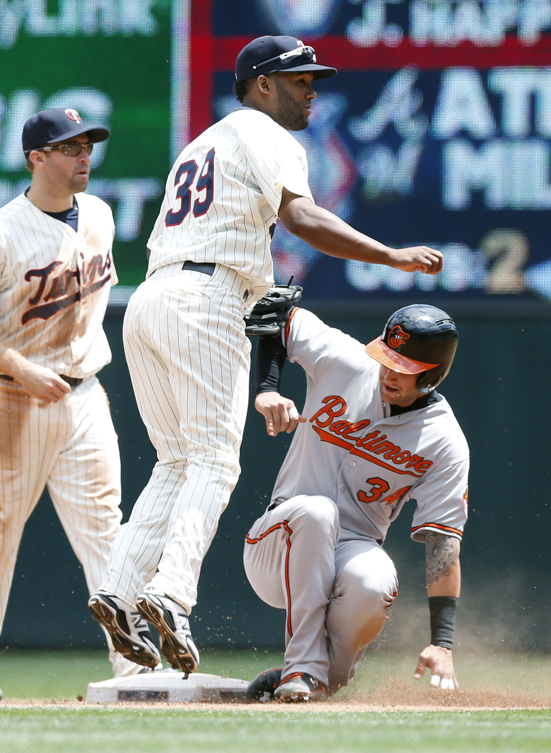 Baltimore Orioles' Christian Walker, right, is forced out at second as shortstop Danny Santana watches his throw to double up J.J. Hardy in the fourth inning of a baseball game, Wednesday, July 8, 2015, in Minneapolis. (AP Photo/Jim Mone)