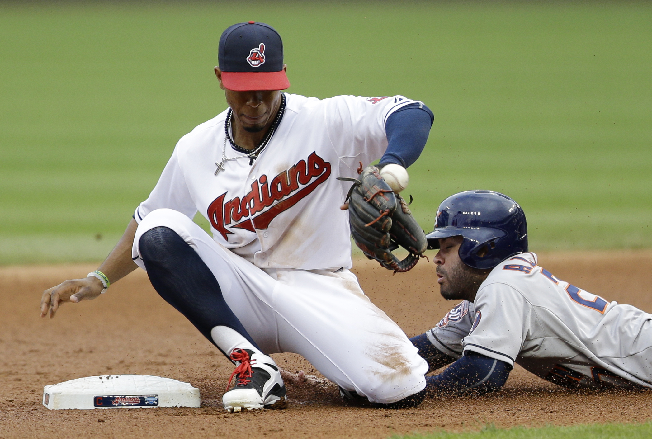 Houston Astros' Jose Altuve slides safely into second base on a wild pitch by Cleveland Indians starting pitcher Trevor Bauer as Francisco Lindor bobbles the ball in the first inning of a baseball game, Wednesday, July 8, 2015, in Cleveland.   (AP Photo/T