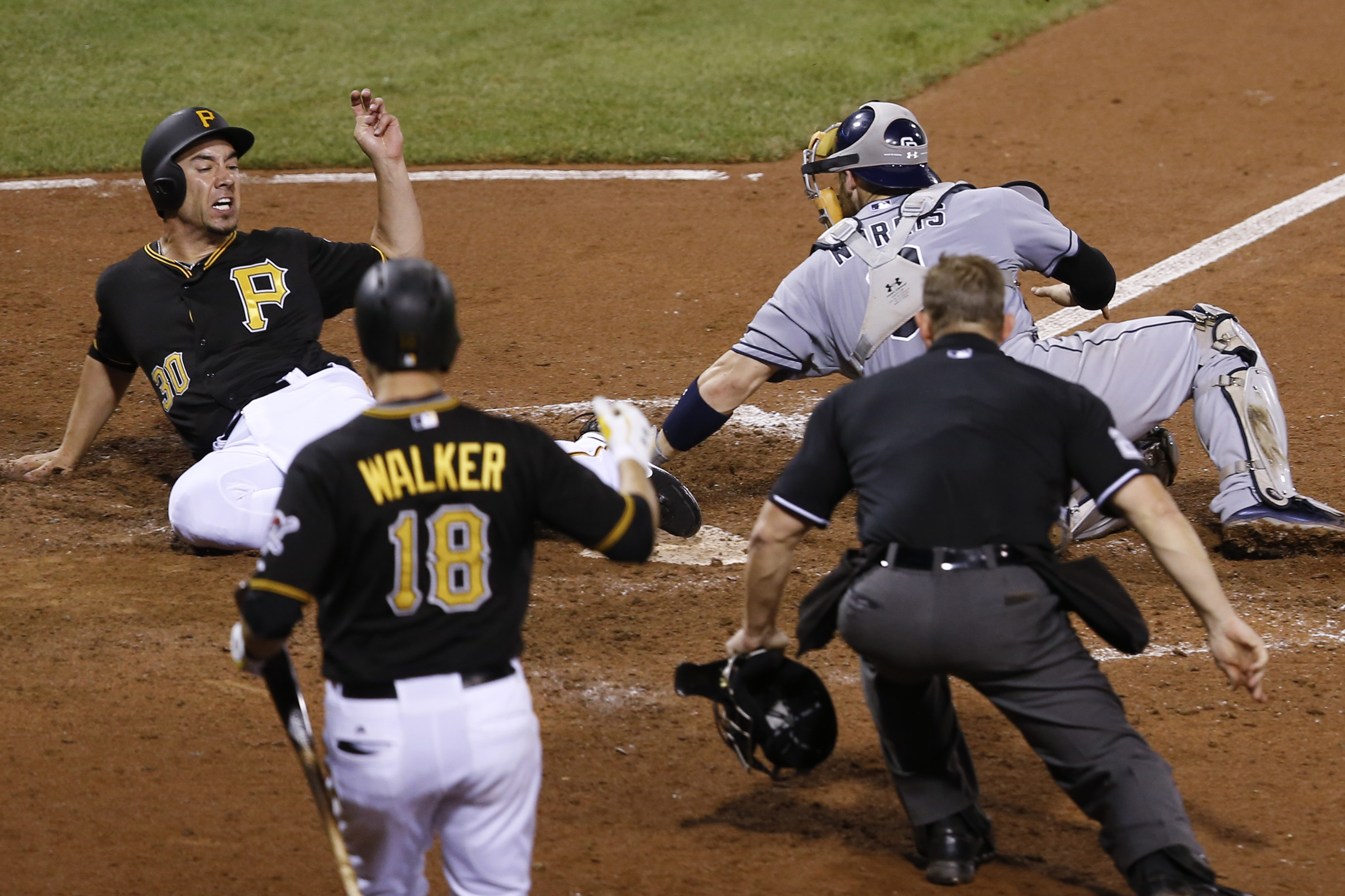 Pittsburgh Pirates' Travis Ishikawa, left, scores on a hit by Gregory Polanco as San Diego Padres catcher Derek Norris reaches to tag him in the eighth inning of a baseball game, Wednesday, July 8, 2015, in Pittsburgh. Neil Walker (18) and home plate umpi