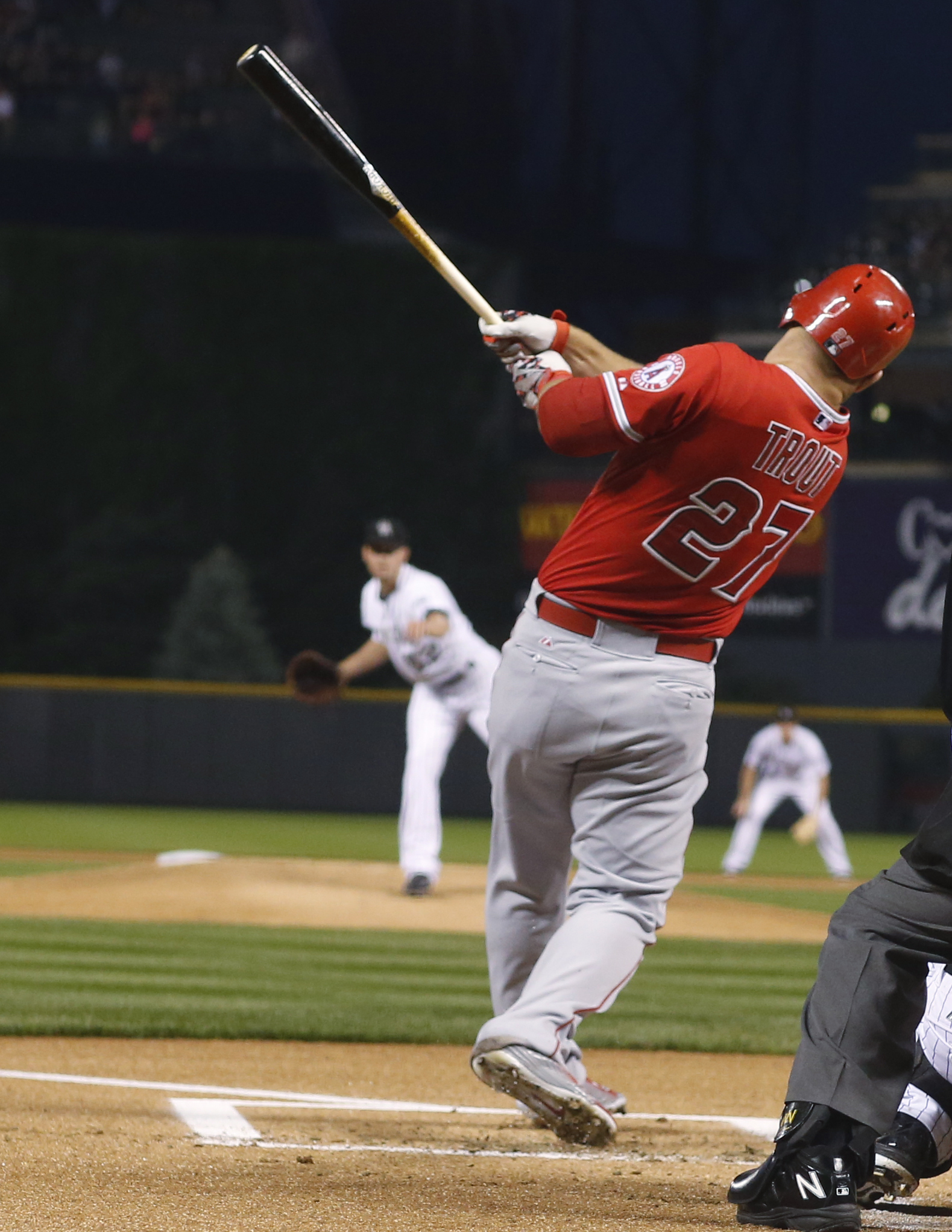 Los Angeles Angels' Mike Trout follows through on a solo home run off Colorado Rockies starting pitcher Chris Rusin during the first inning of a baseball game Wednesday, July 8, 2015, in Denver. (AP Photo/David Zalubowski)