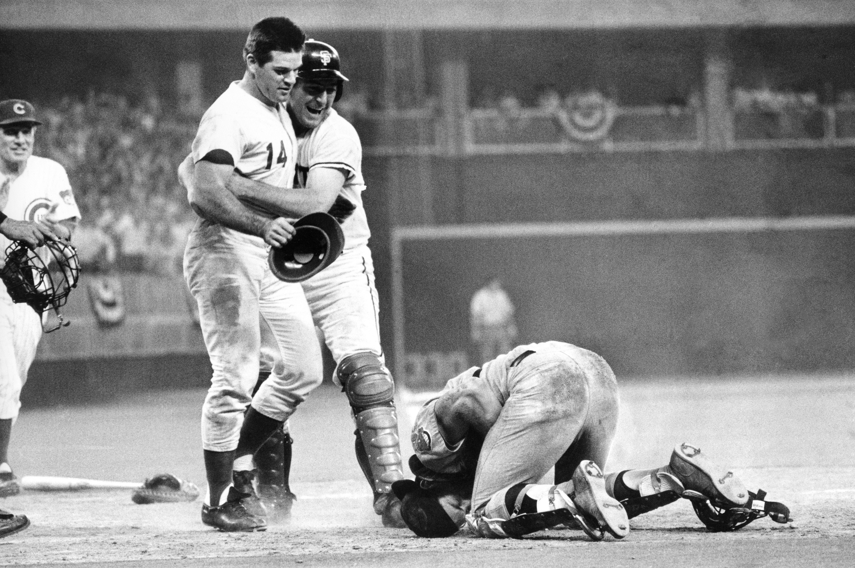 FILE - In this July 14, 1970, file photo, National League's Pete Rose, left, is hugged by his teammate Dick Dietz while American League's catcher Ray Fosse lies injured on the ground, after Rose crashed into him to score the game-winning run for the Natio