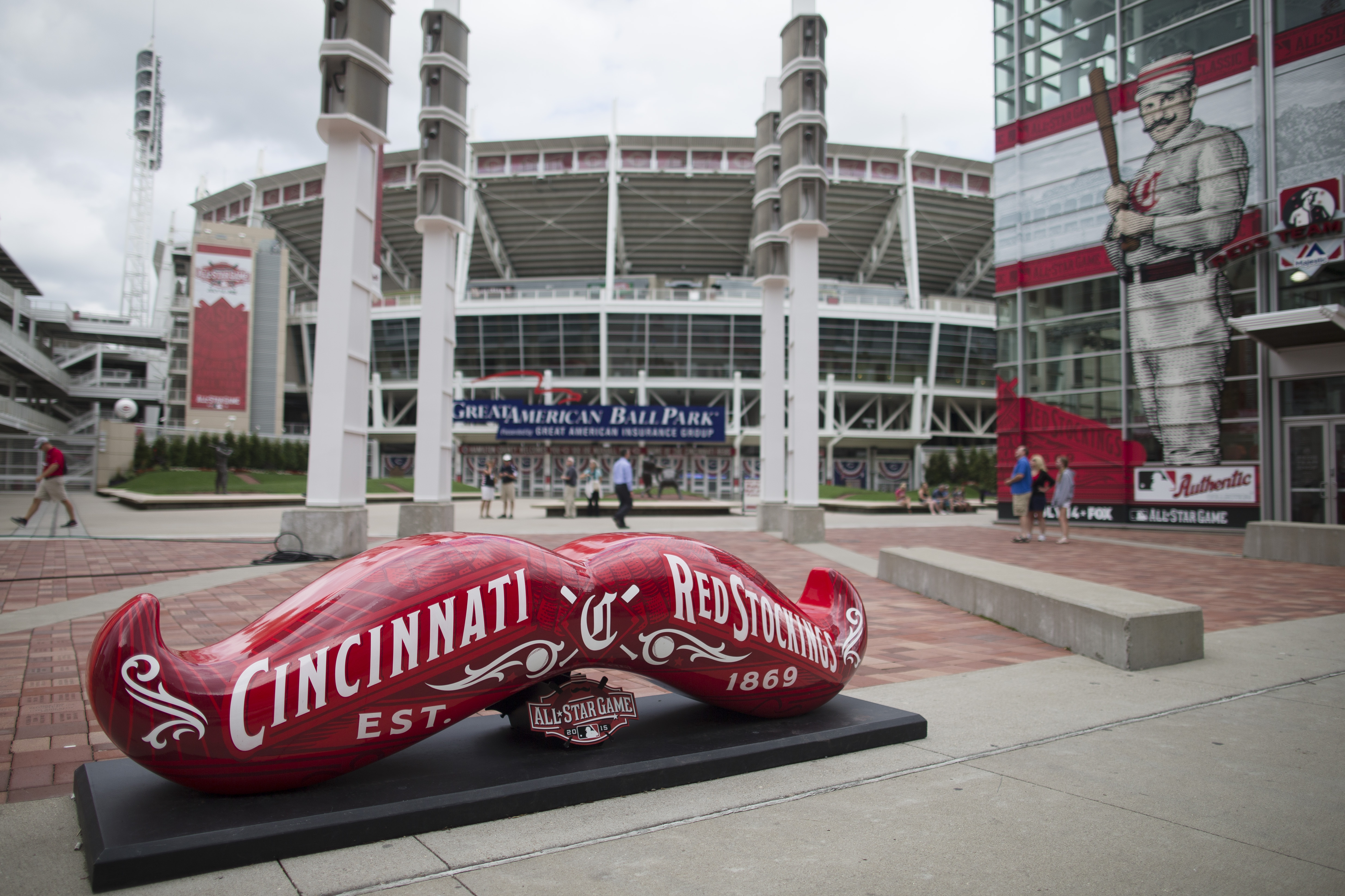 Pedestrians mill about Great American Ball Park as signs advertising the 2015 All-Star Game Baseball game decorate the perimeter, Thursday, July 9, 2015, in Cincinnati. The city is preparing for a weekend of events in the lead-up to the July 14 game. (AP