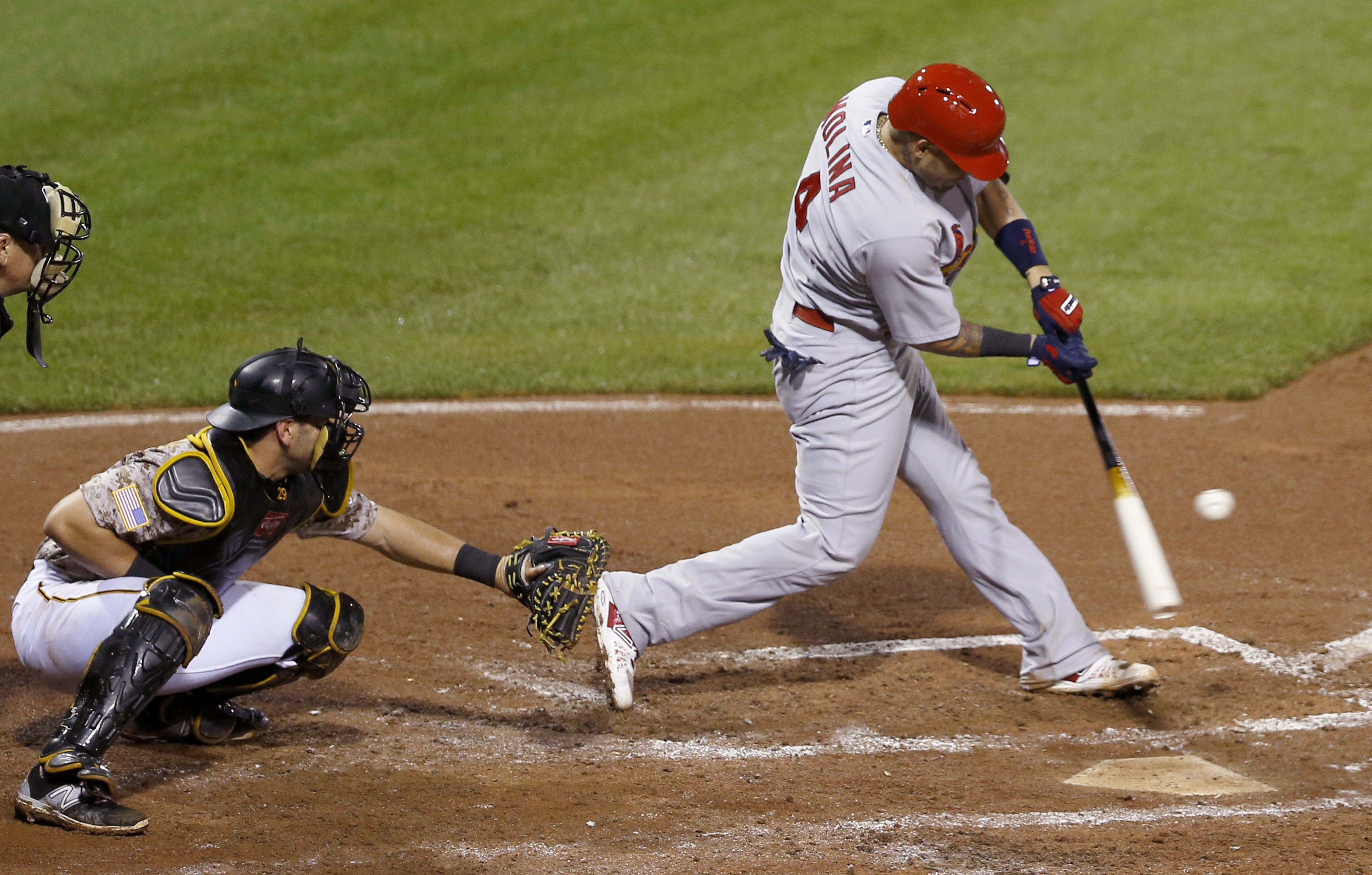 St. Louis Cardinals' Yadier Molina, right, hits a single with the bases loaded in front of Pittsburgh Pirates catcher Francisco Cervelli to drive in two runs during the fifth inning of a baseball game, Thursday, July 9, 2015, in Pittsburgh. (AP Photo/Keit