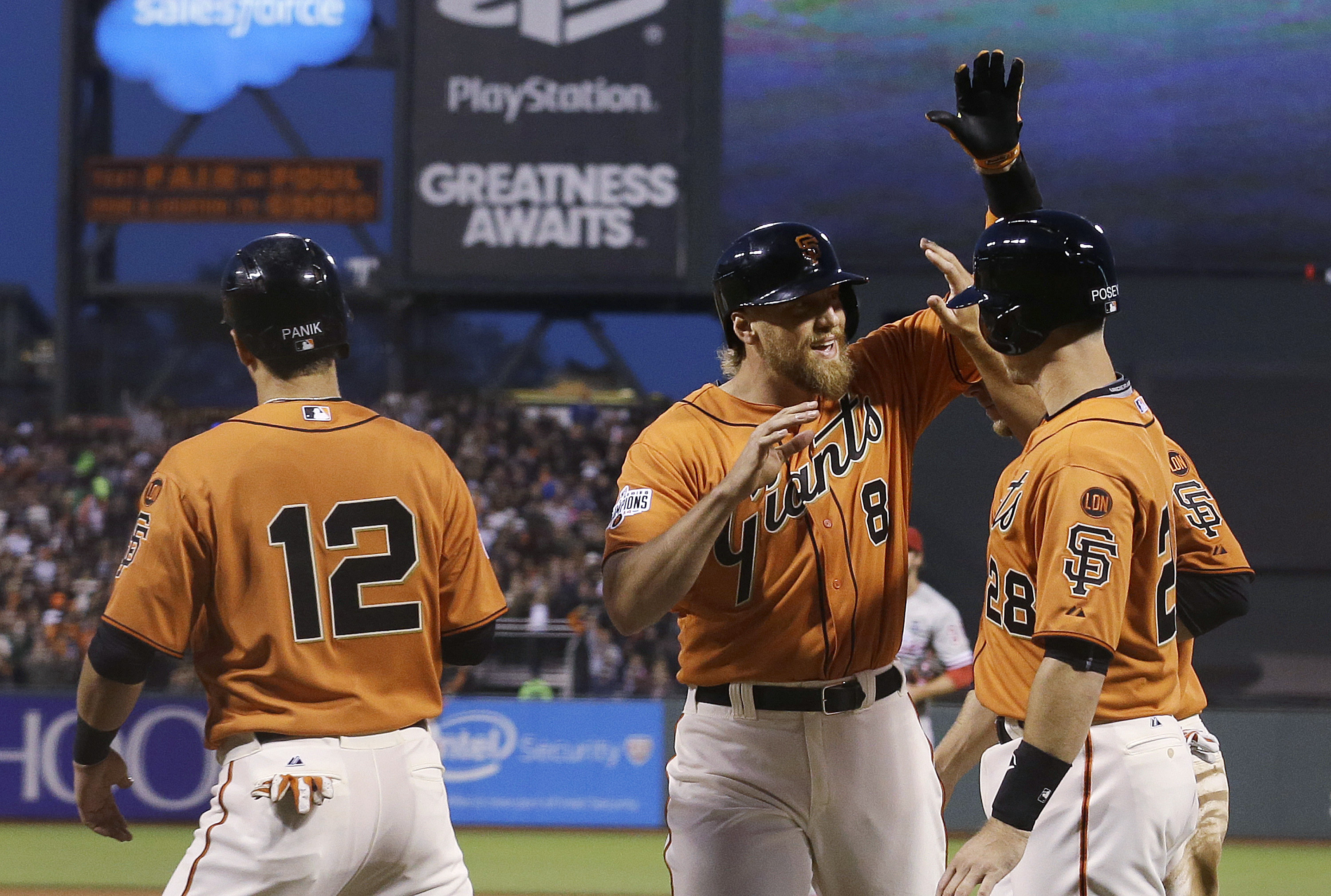 San Francisco Giants' Hunter Pence (8) is congratulated,after hitting a grand slam off Philadelphia Phillies pitcher Cole Hamels, by Joe Panik (12), Buster Posey (28) and Matt Duffy, hidden, during the fourth inning of a baseball game in San Francisco, Fr
