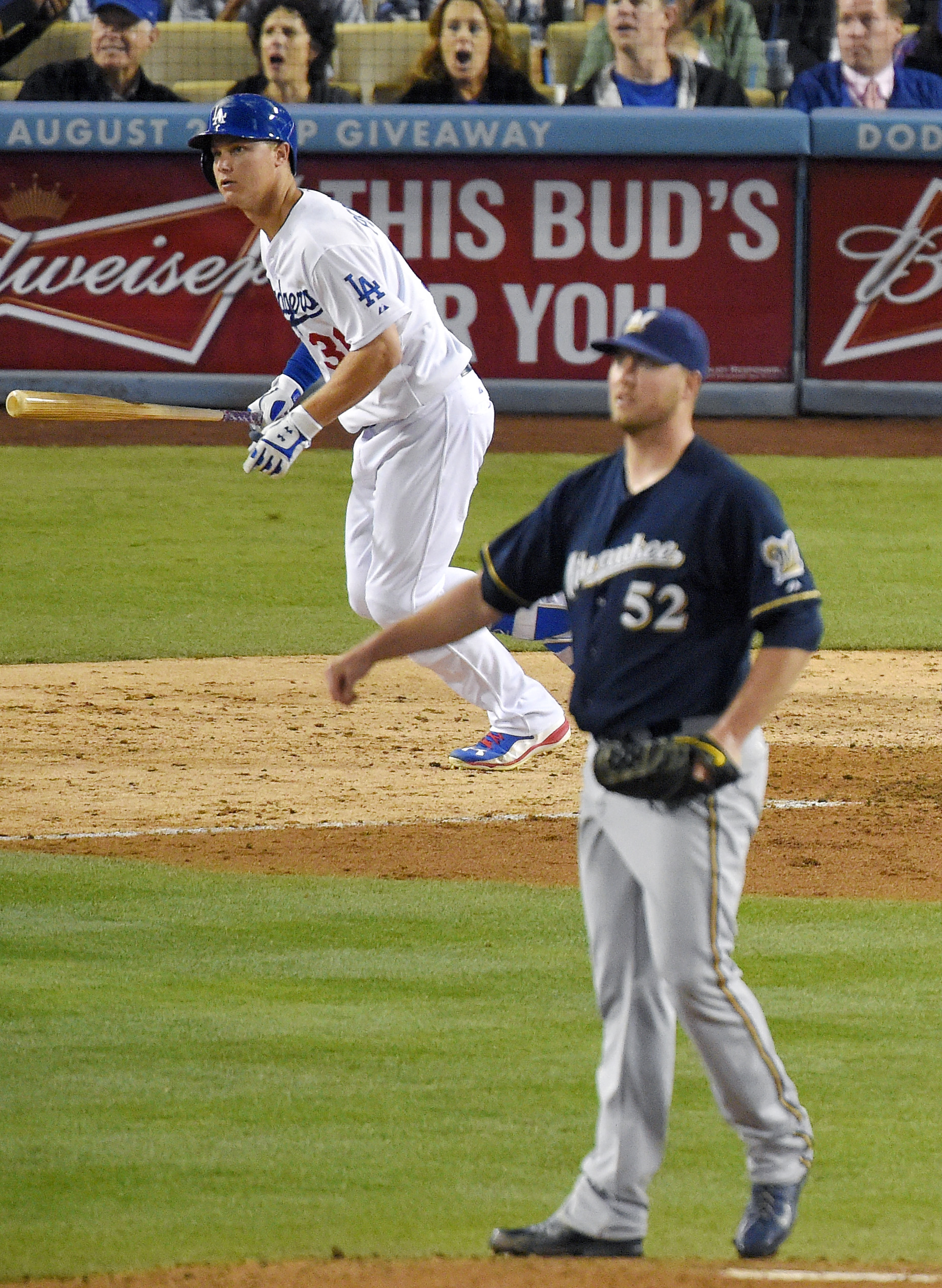 Los Angeles Dodgers' Joc Pederson runs to first on a single off Milwaukee Brewers starting pitcher Jimmy Nelson, foreground, during the sixth inning of a baseball game, Friday, July 10, 2015, in Los Angeles.  (AP Photo/Mark J. Terrill)