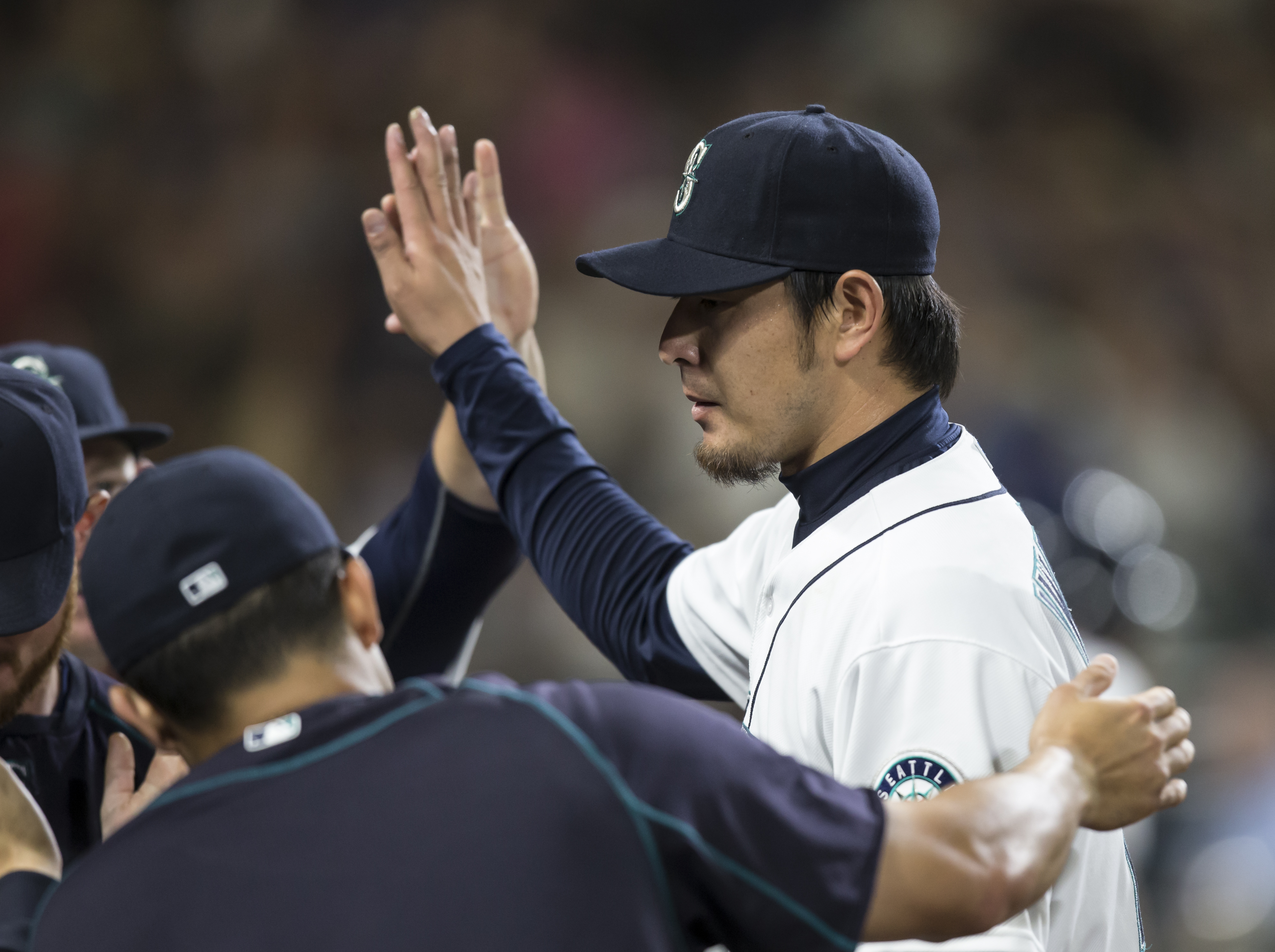 Seattle Mariners starter Hisashi Iwakuma is congratulated by teammates as he comes off the field after the top of the eighth inning of a baseball game against the Los Angeles Angels, Saturday, July 11, 2015, in Seattle. (AP Photo/Stephen Brashear)