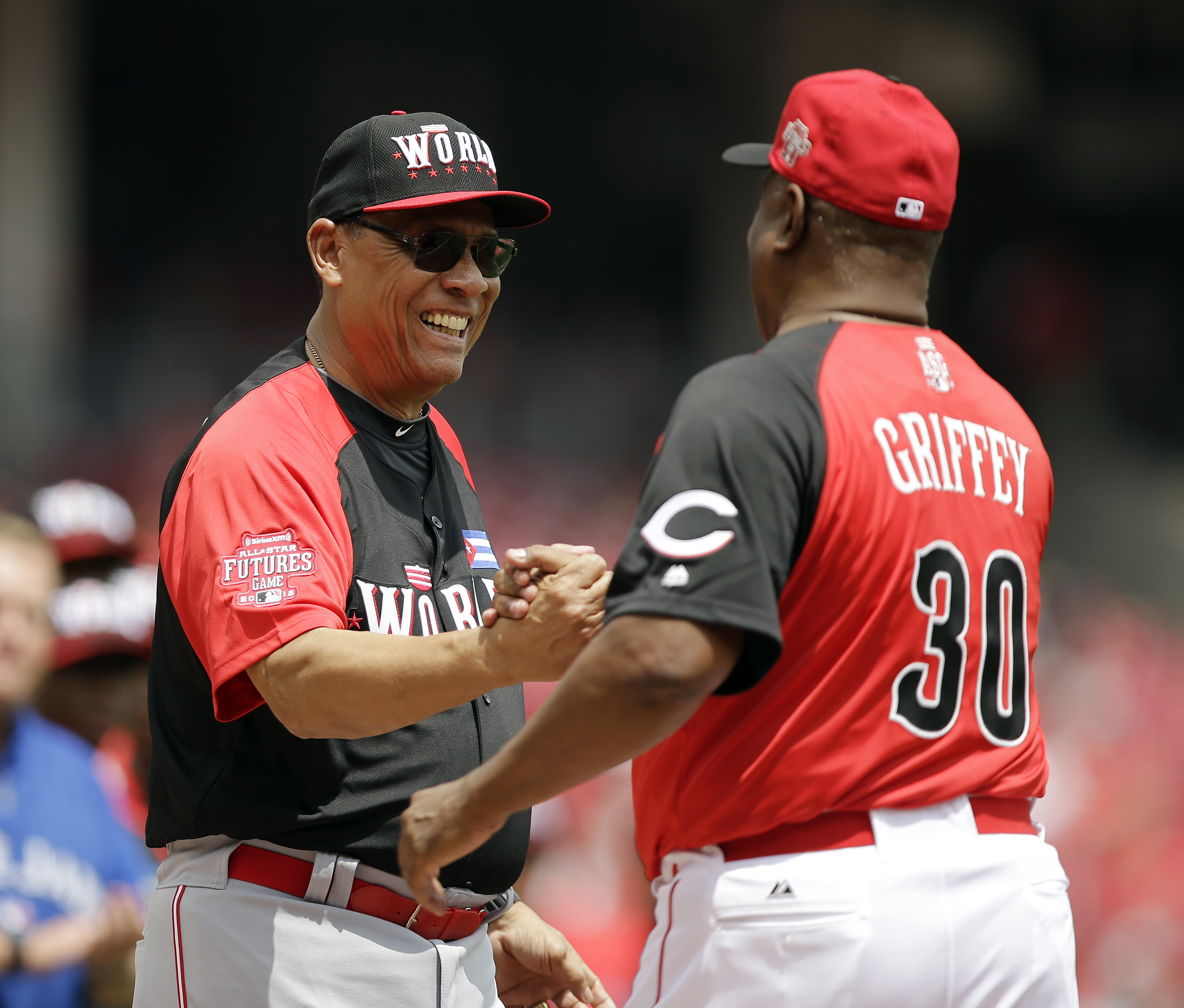 Team World manager Tony Perez, left, greets Team United States manager Ken Griffey Sr. before the All-Star Futures baseball game, Sunday, July 12, 2015, in Cincinnati. (AP Photo/Darron Cummings)