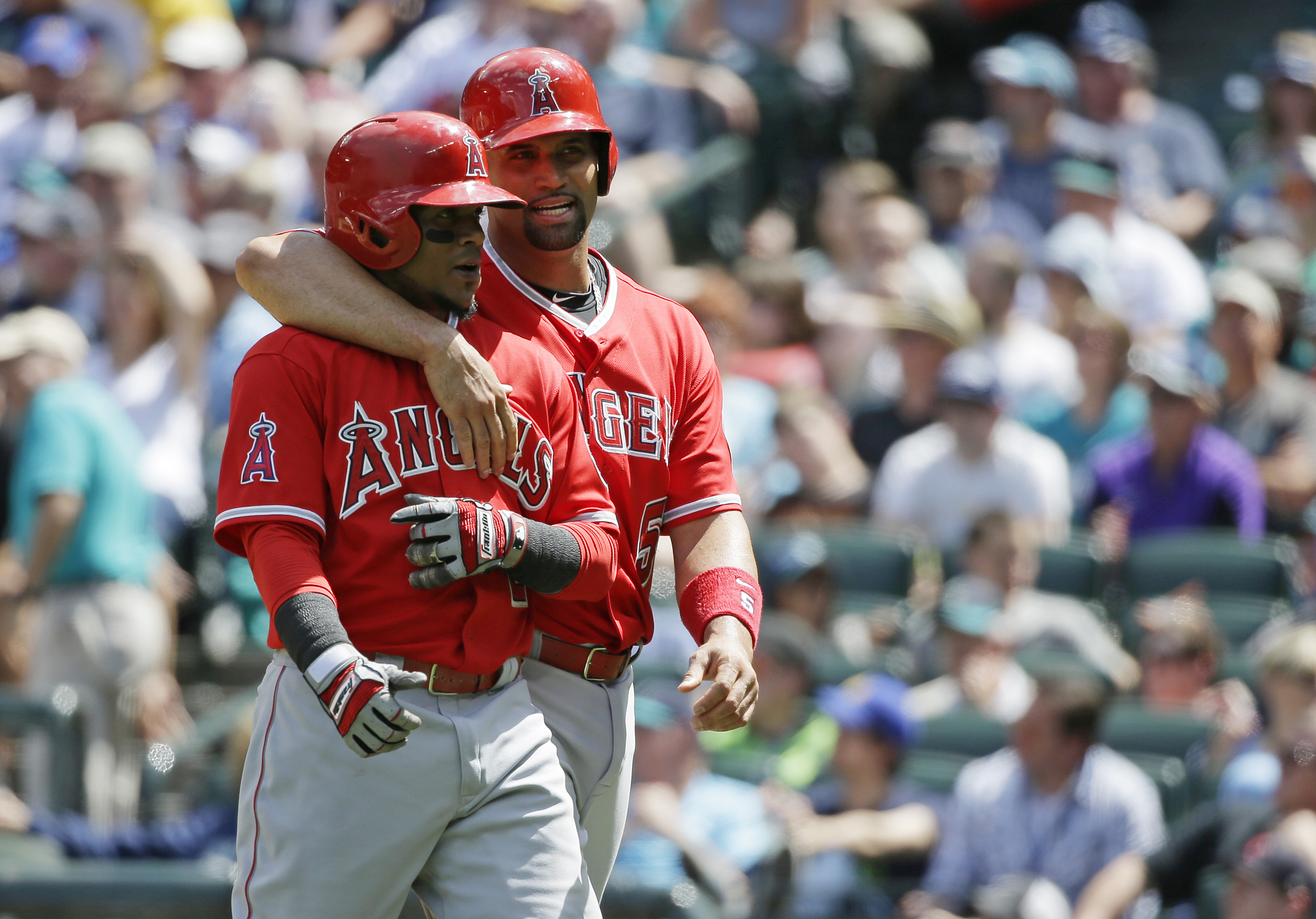 Los Angeles Angels' Albert Pujols, right, walks with Erick Aybar, left, after they both scored on a double hit by teammate David Freese in the sixth inning of a baseball game against the Seattle Mariners, Sunday, July 12, 2015, in Seattle. (AP Photo/Ted S