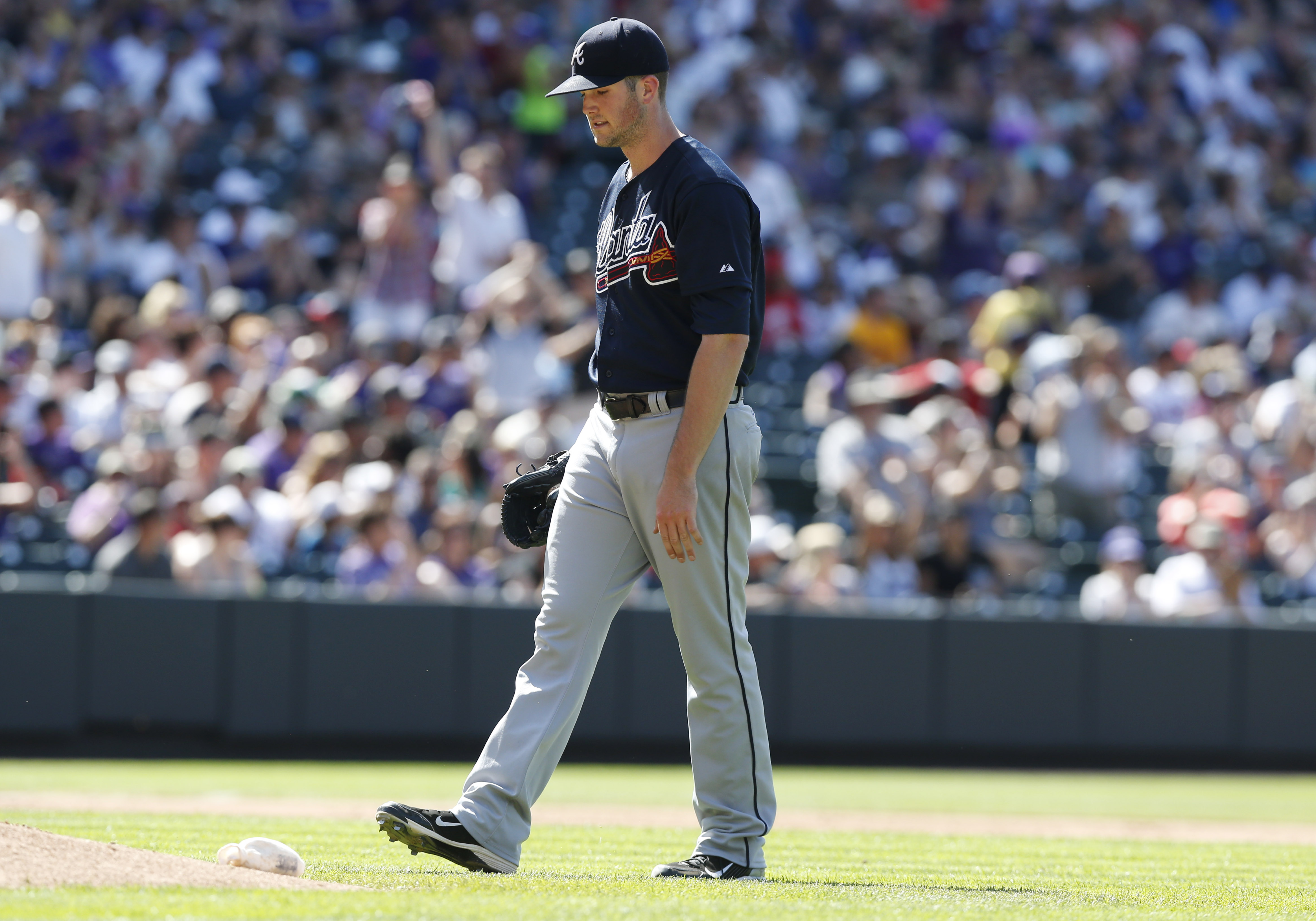 Atlanta Braves starting pitcher Alex Wood reacts after giving up a single to drive in two runners to Colorado Rockies' Charlie Blackmon in the sixth inning of a baseball game Sunday, July 12, 2015, in Denver. (AP Photo/David Zalubowski)