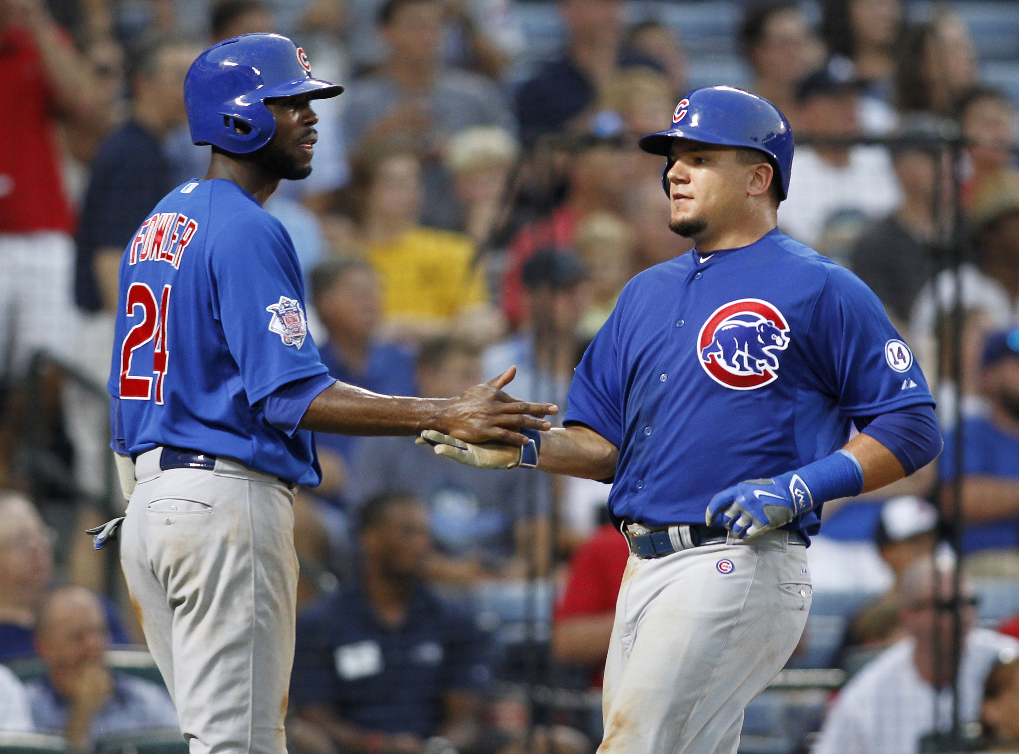 Chicago Cubs' Dexter Fowler (24) and Kyle Schwarber celebrate after scoring on a Jorge Soler single during the third inning of a baseball game against the Atlanta Braves, Friday, July 17, 2015, in Atlanta. (AP Photo/Brett Davis)