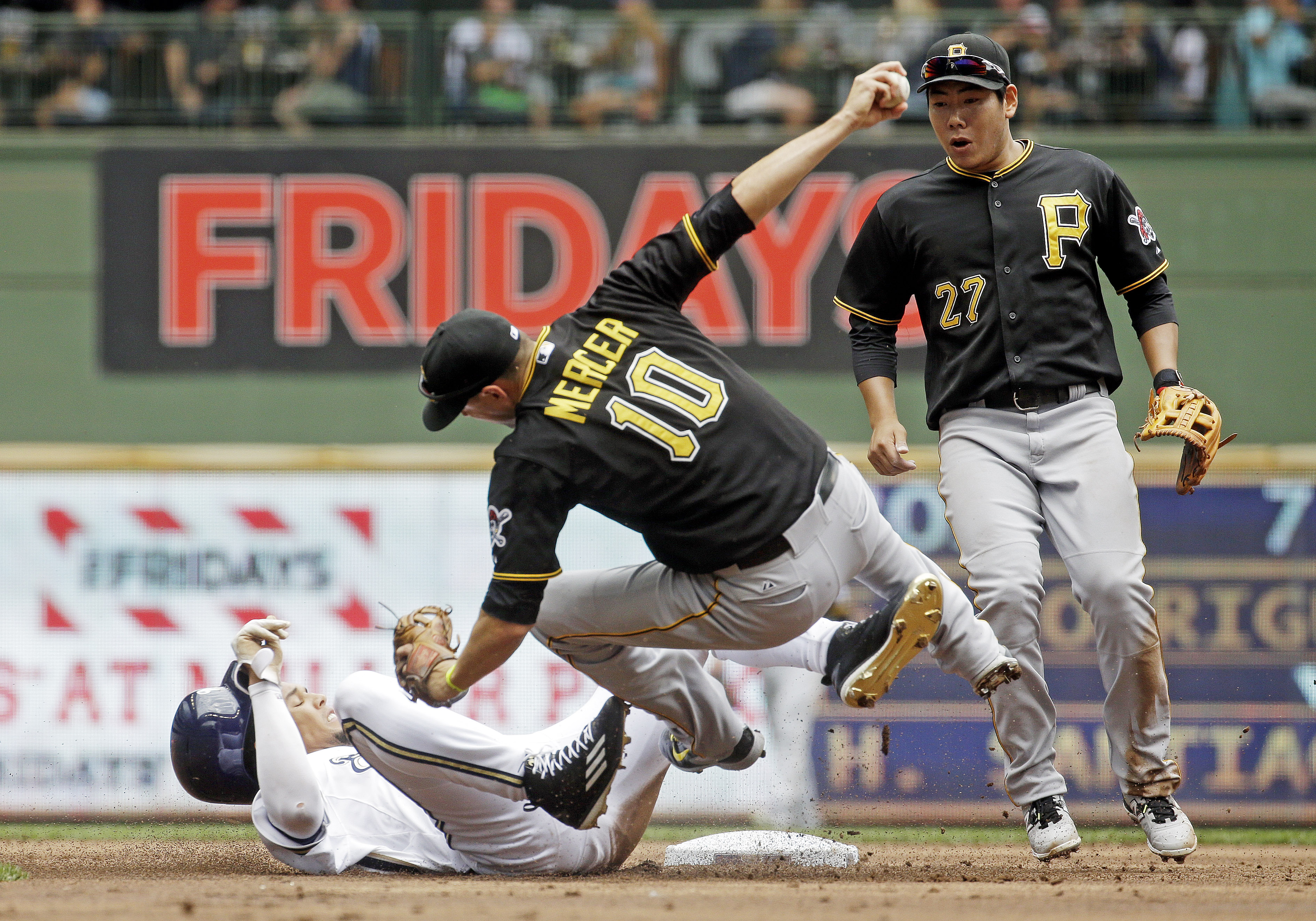 Pittsburgh Pirates' Jung Ho Kang (27) watches as teammate Jordy Mercer (10) collides with Milwaukee Brewers' Carlos Gomez during the second inning of a baseball game Sunday, July 19, 2015, in Milwaukee. Gomez was out on the play and Mercer left the game o